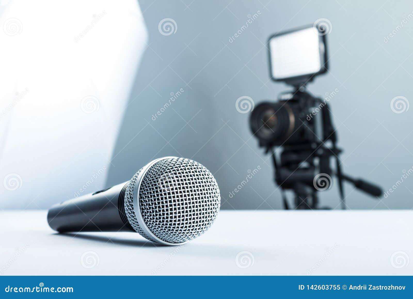 Bezprzewodowy mikrofonu lying on the beach na białym stole przeciw tłu DSLR kamera dowodzony światło