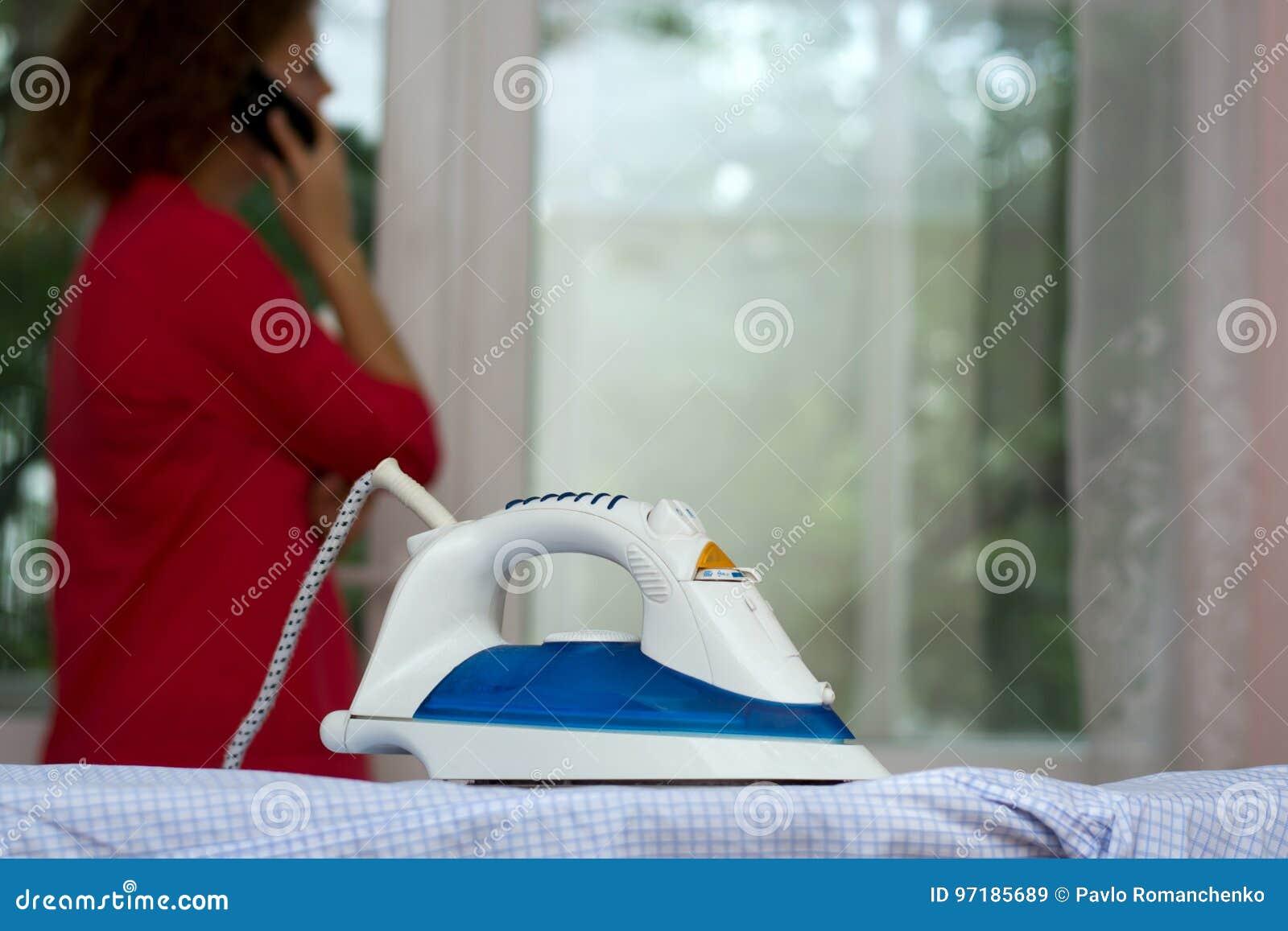 Beztroska dziewczyna opowiada na telefonie zapomina o żelazie na prasowanie desce