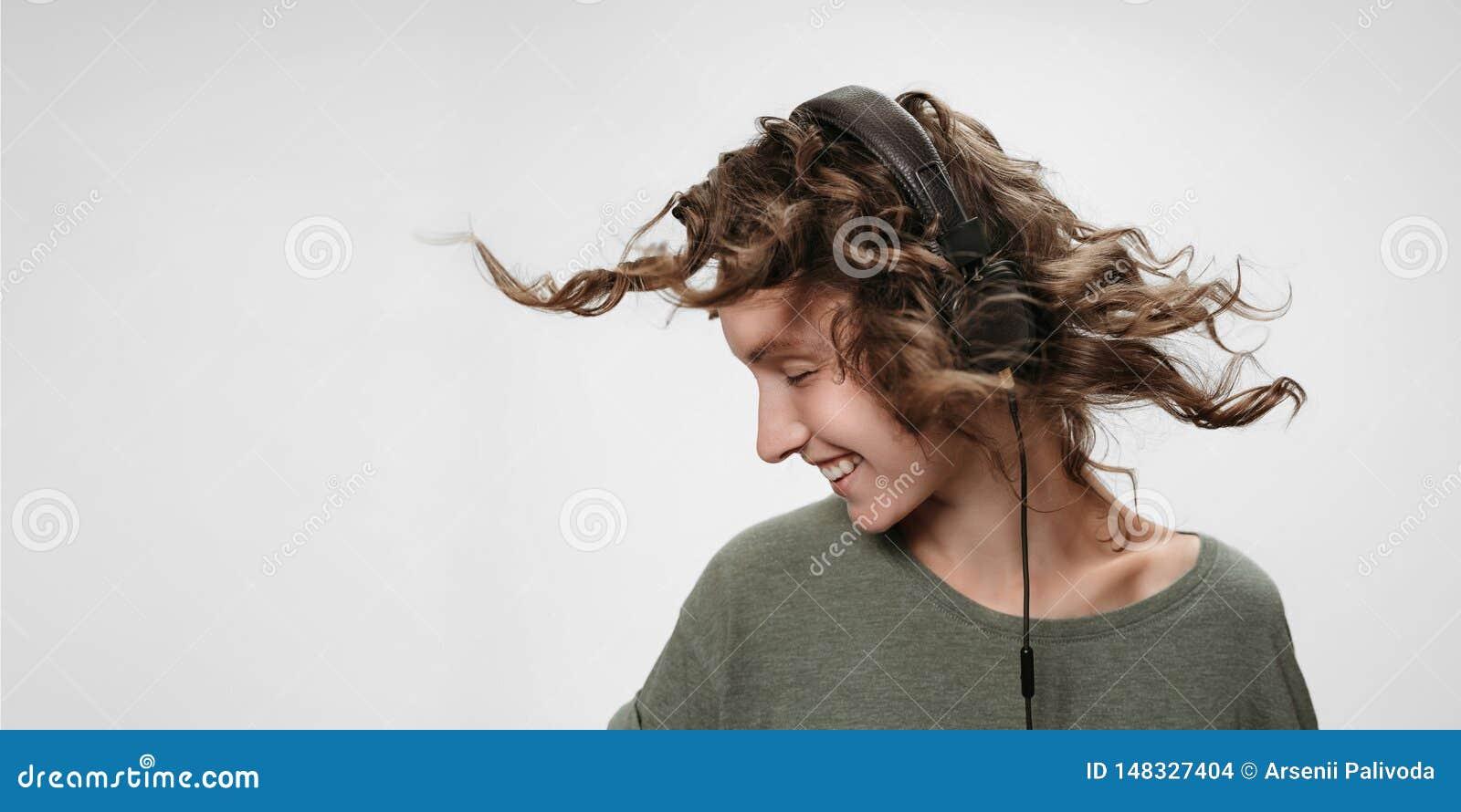 Beztroska rozochocona m?oda k?dzierzawa kobieta s?ucha ulubion? muzyk?