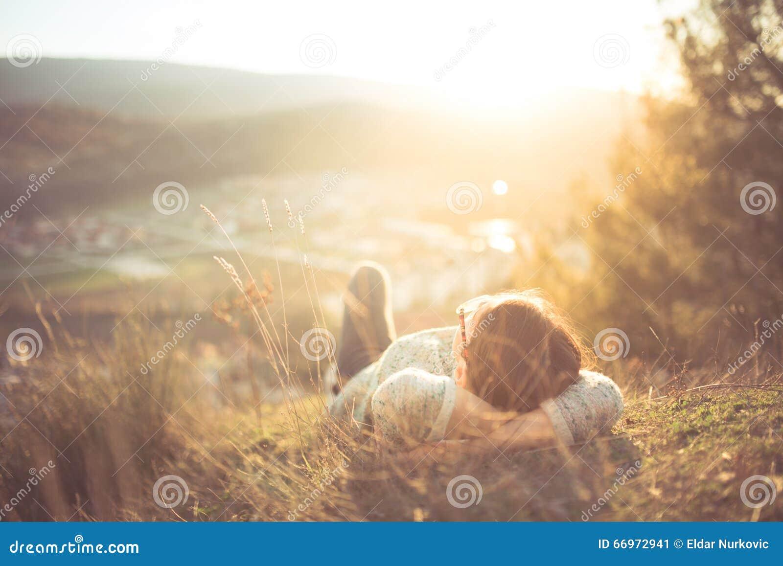 Beztroski szczęśliwy kobiety lying on the beach na zielonej trawy łące na górze halnej krawędzi falezy cieszy się słońce na jej t