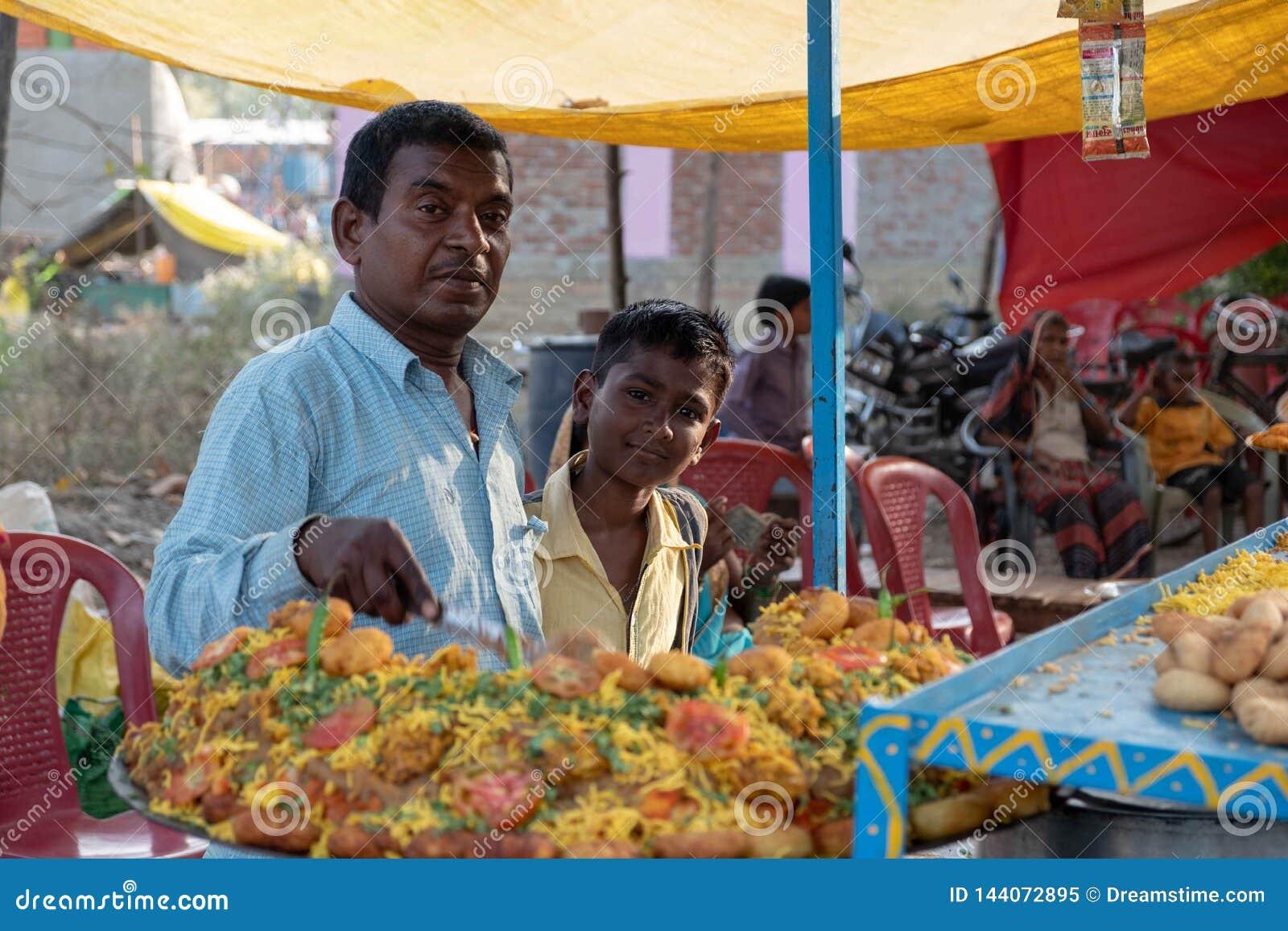 Bhadarsa, Uttar Pradesh/Índia - 3 de abril de 2019: Um homem levanta para uma foto com seu filho ao fazer o alimento da rua em um