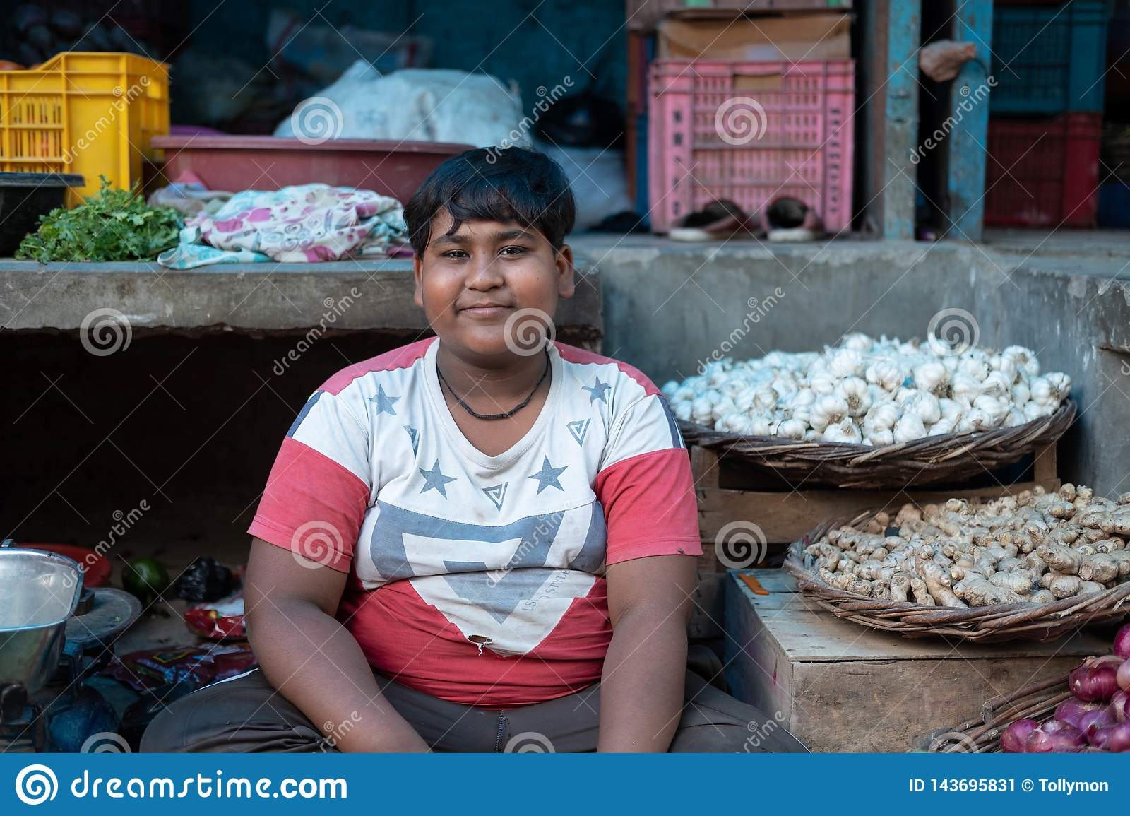 Bhadarsa, Uttar Pradesh / India - April 2, 2019: A boy poses for a photo in his family`s vegetable stall in Bhadarsa.