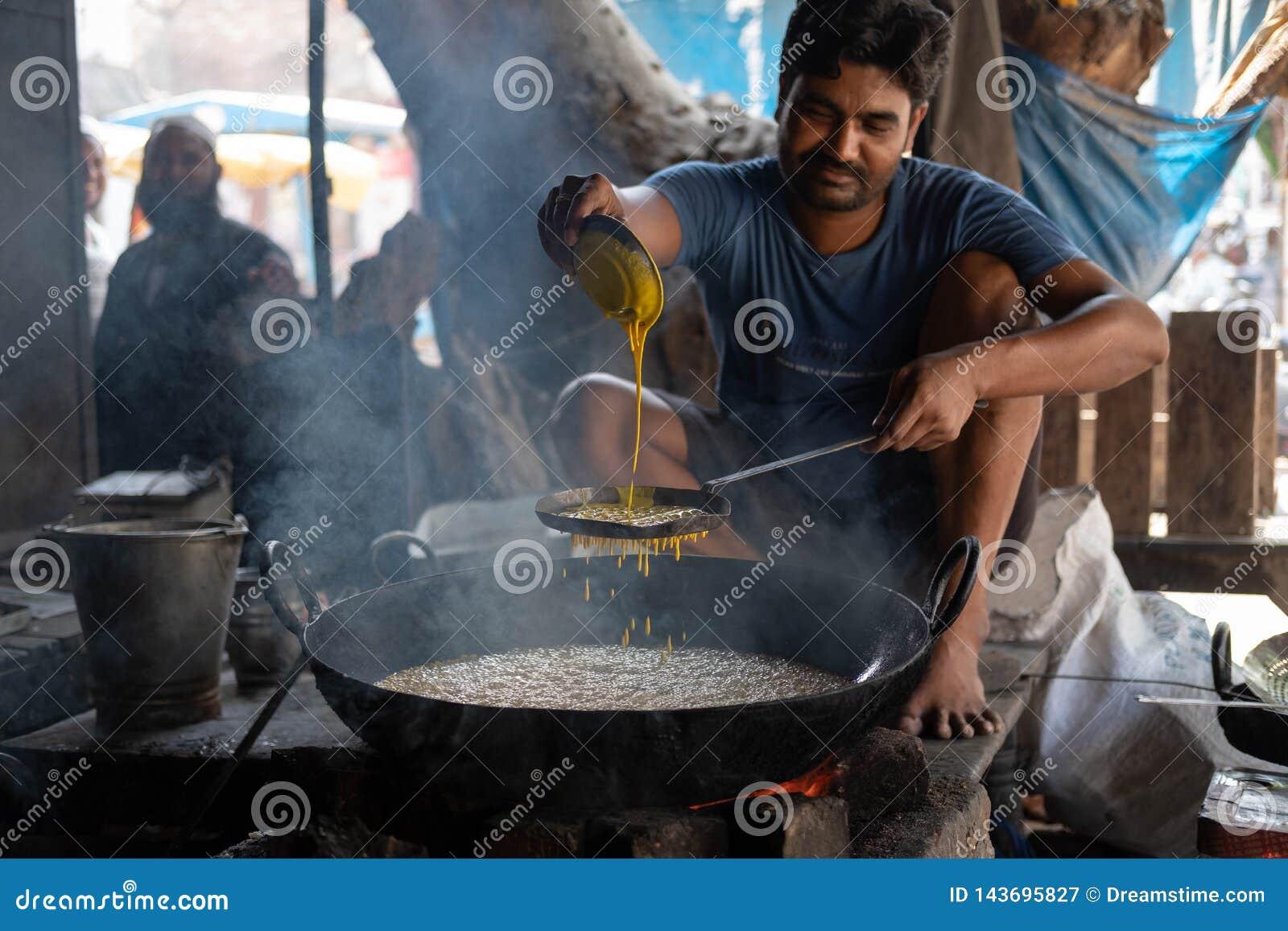Bhadarsa, Uttar Pradesh / India - April 2, 2019: A man frys up jalebi street side in Bhadarsa.