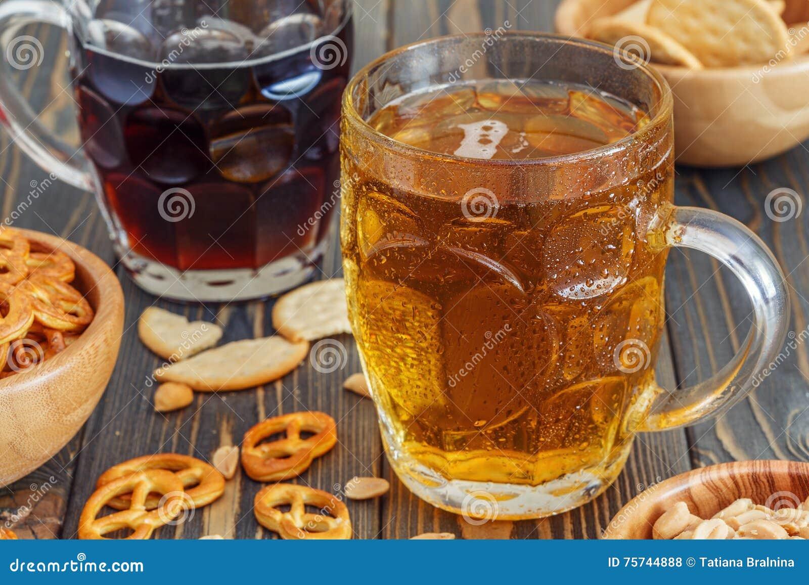 Bière avec des bretzels, des biscuits et des écrous