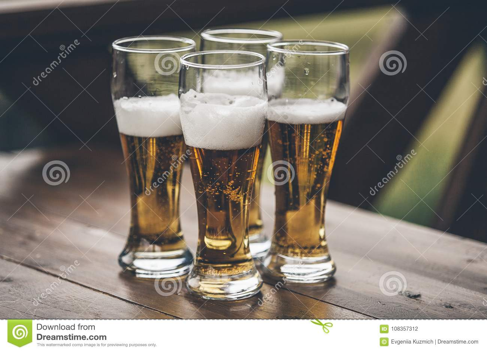 Bière avec les garçons grands de lumière de mousse se tenant sur un closeu en bois de table
