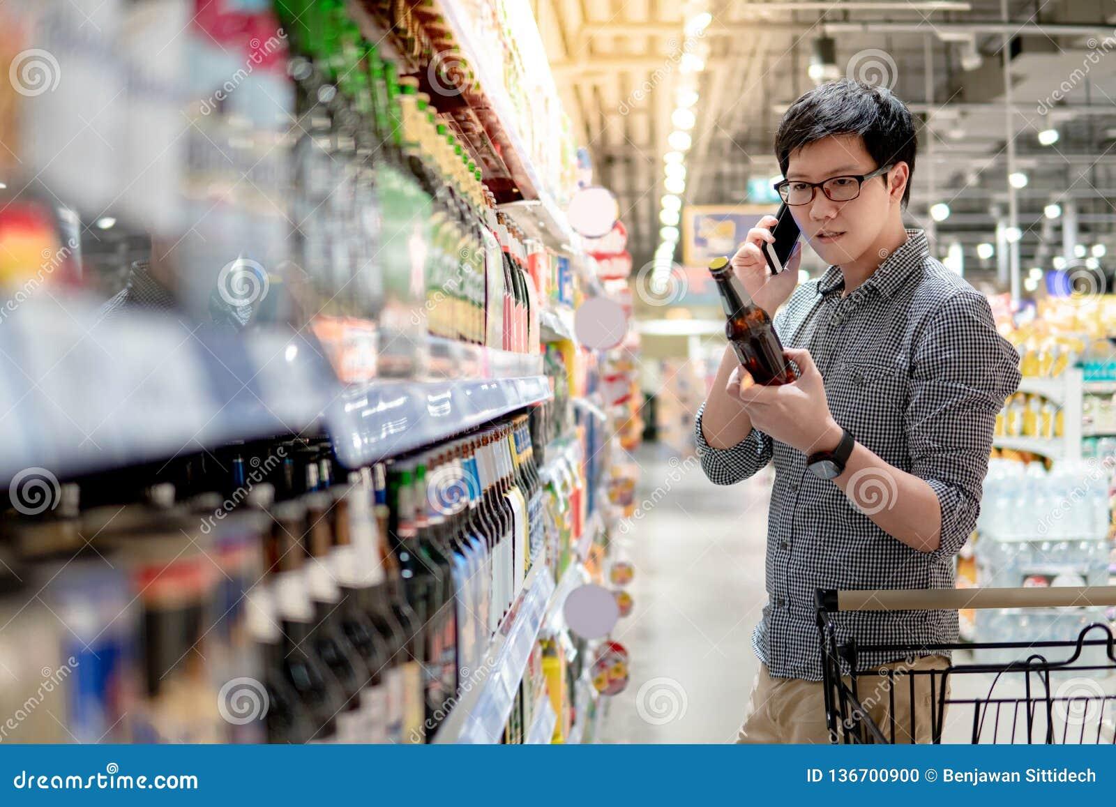 Bière de achat d homme asiatique utilisant le téléphone
