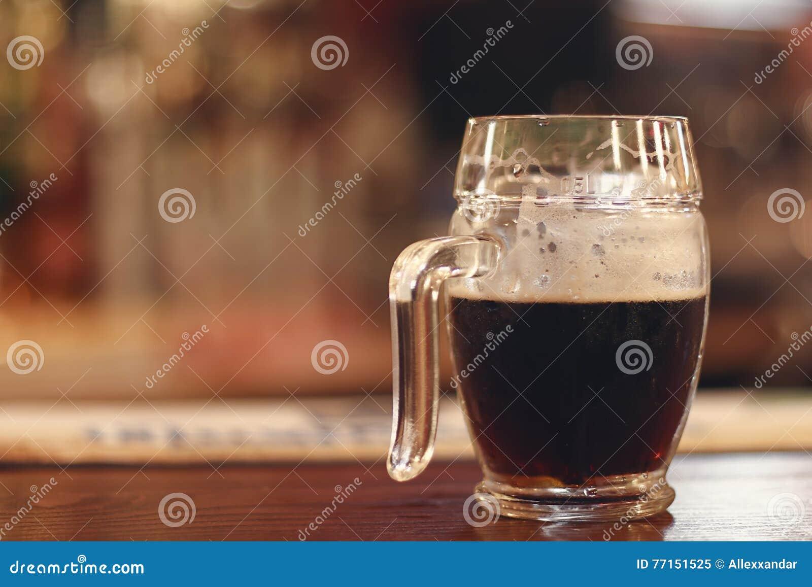 Bière noire sur la table en bois Demi bière de noir de tasse