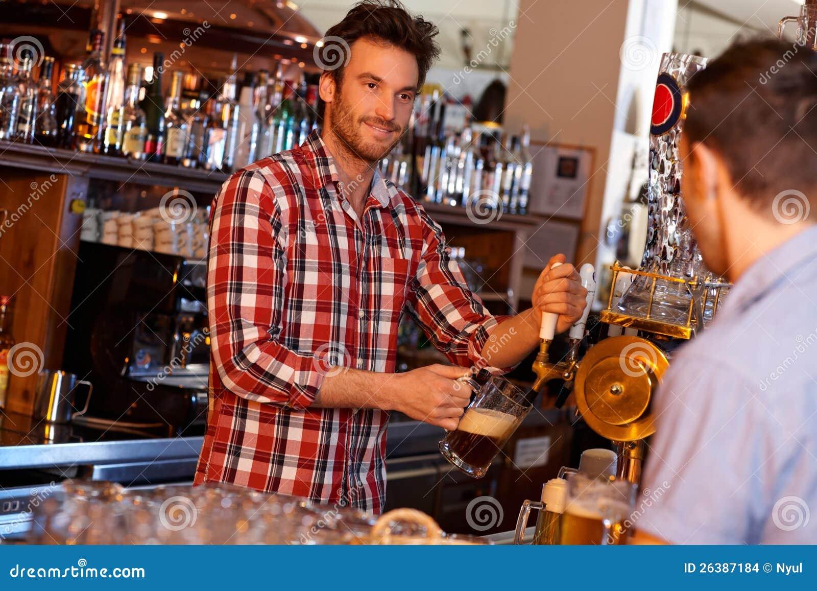 Bière pression de portion de barman dans le bar