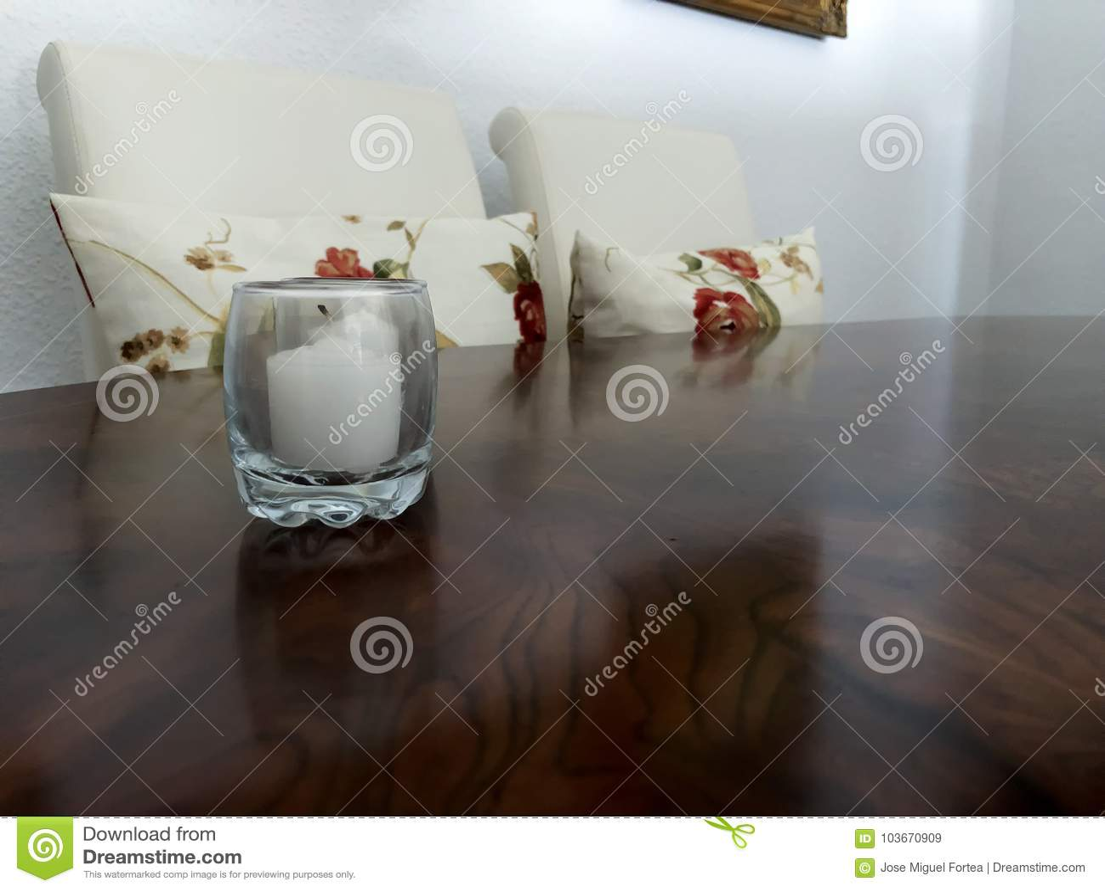 Biała świeczka na drewnianym stole z białymi krzesłami