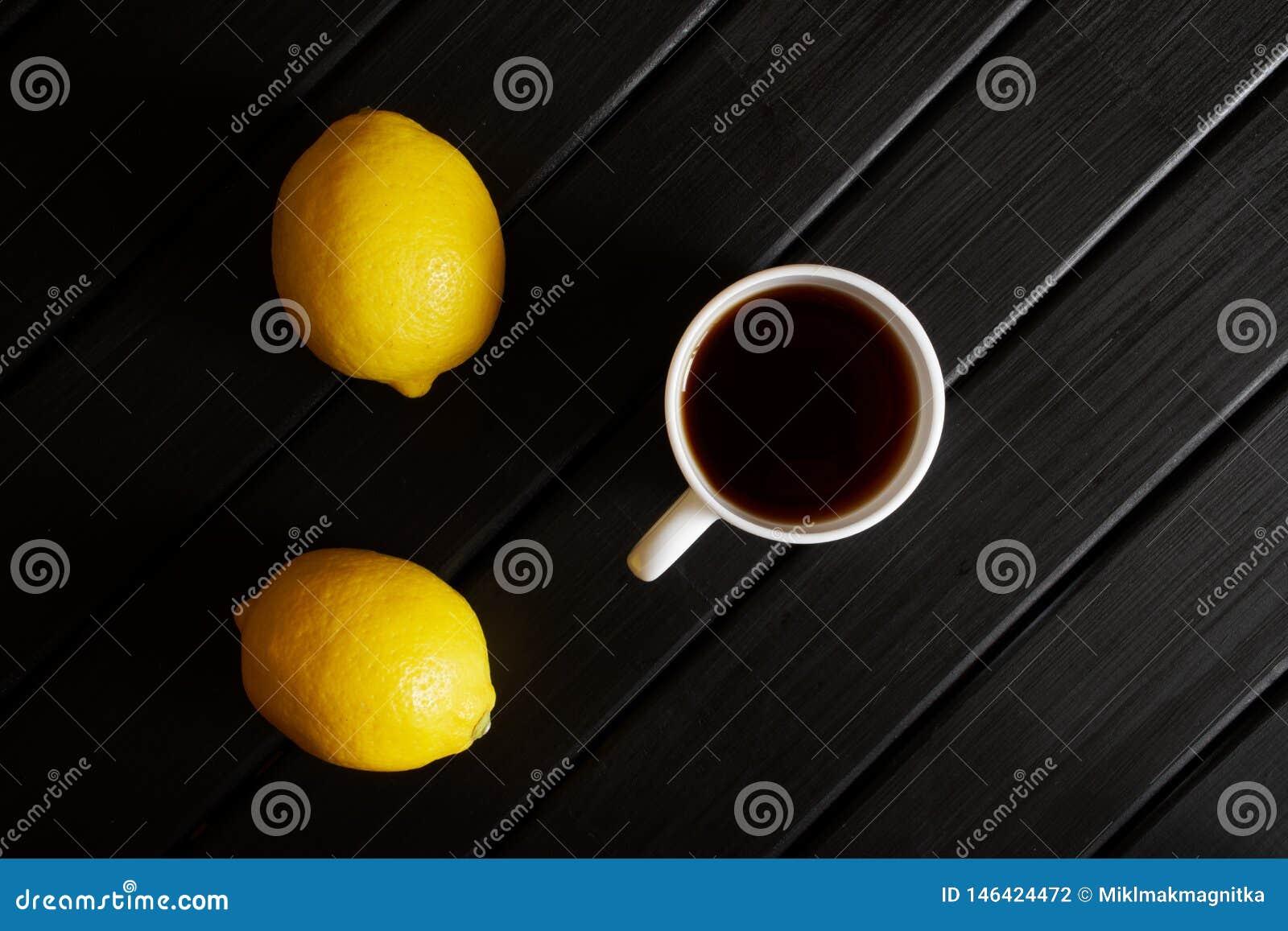 Biała filiżanka z czarnej herbaty stojakami na czarnym stole obok dwa żółtych cytryn minimalista ?wiat?o dzienne