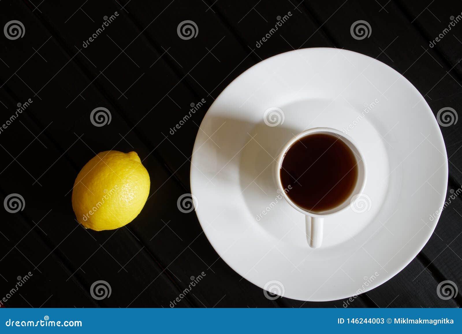 Biała filiżanka z czarnej herbaty stojakami w spodeczku obok żółtej cytryny na ciemnym drewnianym stole na widok minimalista