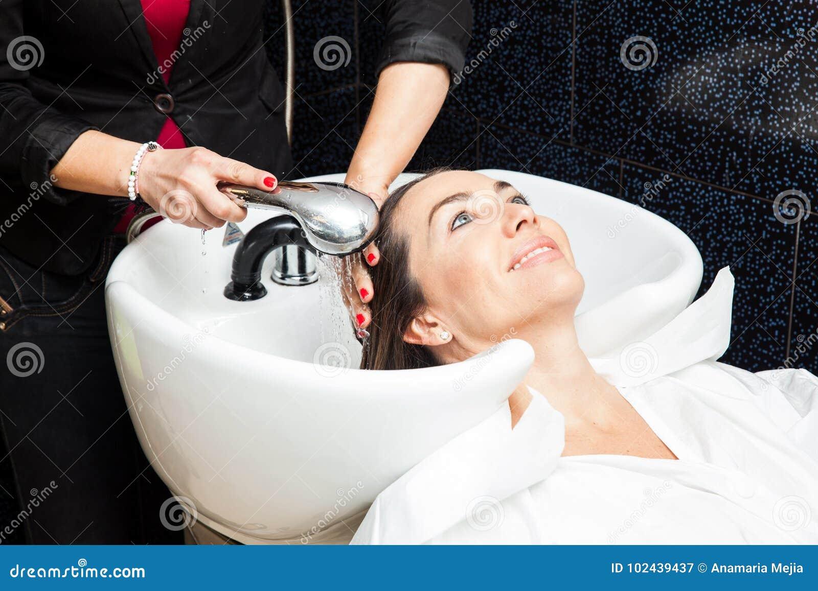 Biała kobieta dostaje włosianego obmycie w piękno salonie