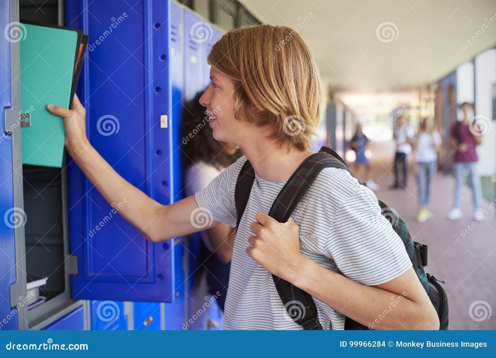 Biała nastoletnia uczniowska używa szafka w szkolnym korytarzu