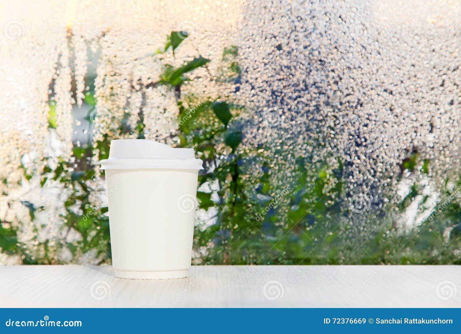 Biała rozporządzalna filiżanka na stołowym zbliża deszczowego dnia okno tle