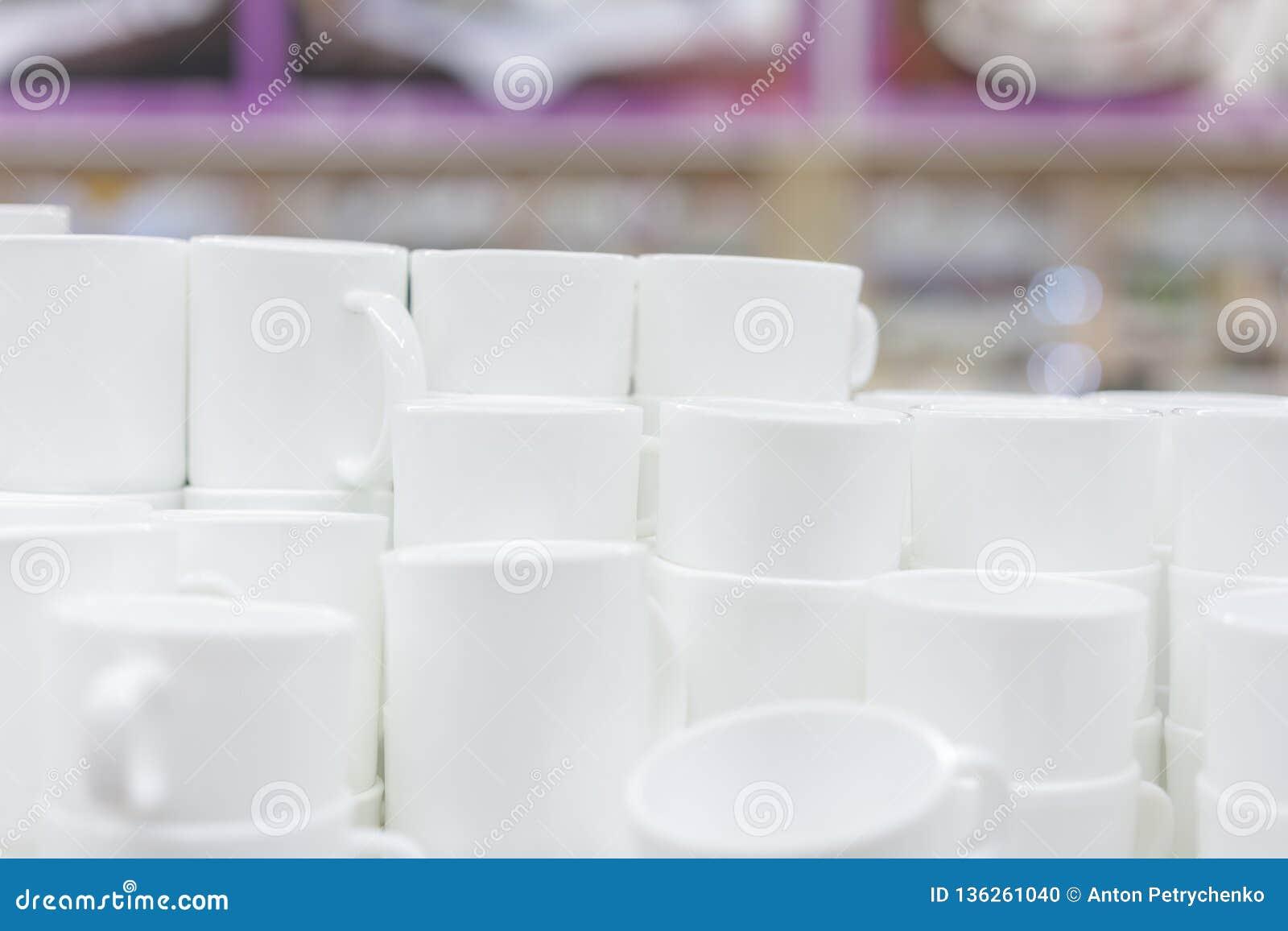Białe filiżanki na półce w sklepie Biali ceramiczni spodeczki na półkach i filiżanki Półki z kuchennymi naczyniami