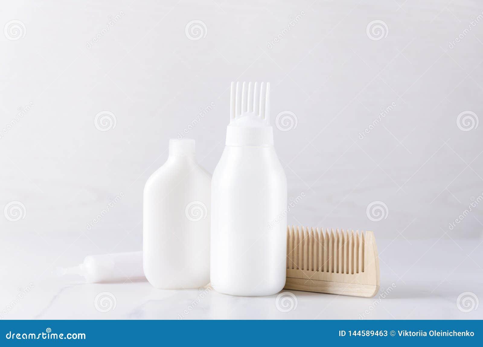 Białe klingeryt butelki z włosianej opieki produktami, drewniana grępla :