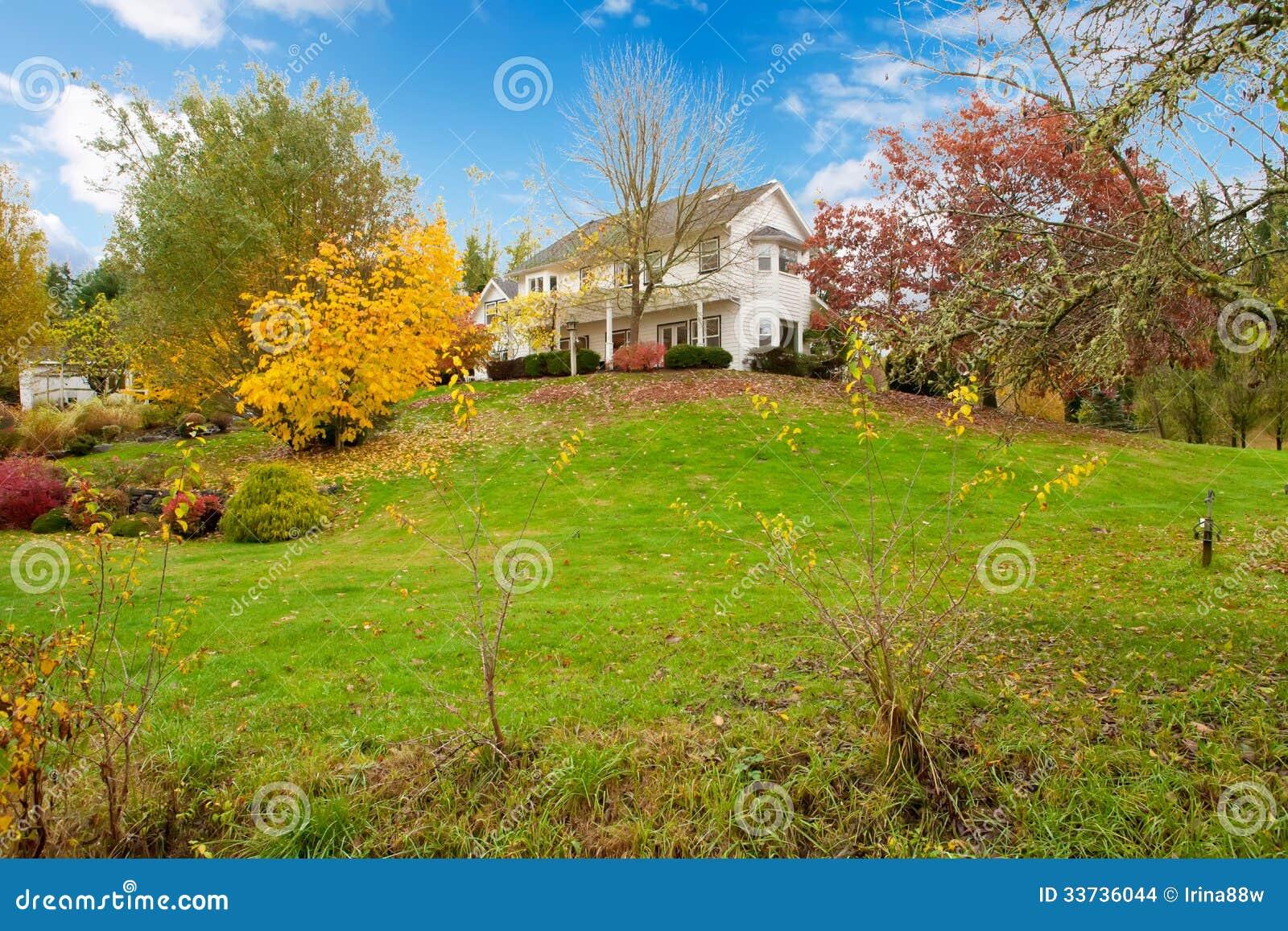 Białego konia gospodarstwa rolnego amerykanina dom podczas spadku z zieloną trawą.