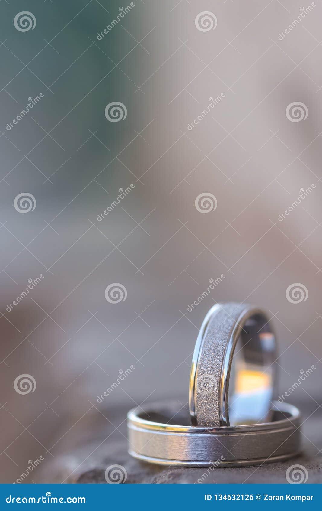 Białego złota obrączek ślubnych stojak na czarnej skale zamazujący tło