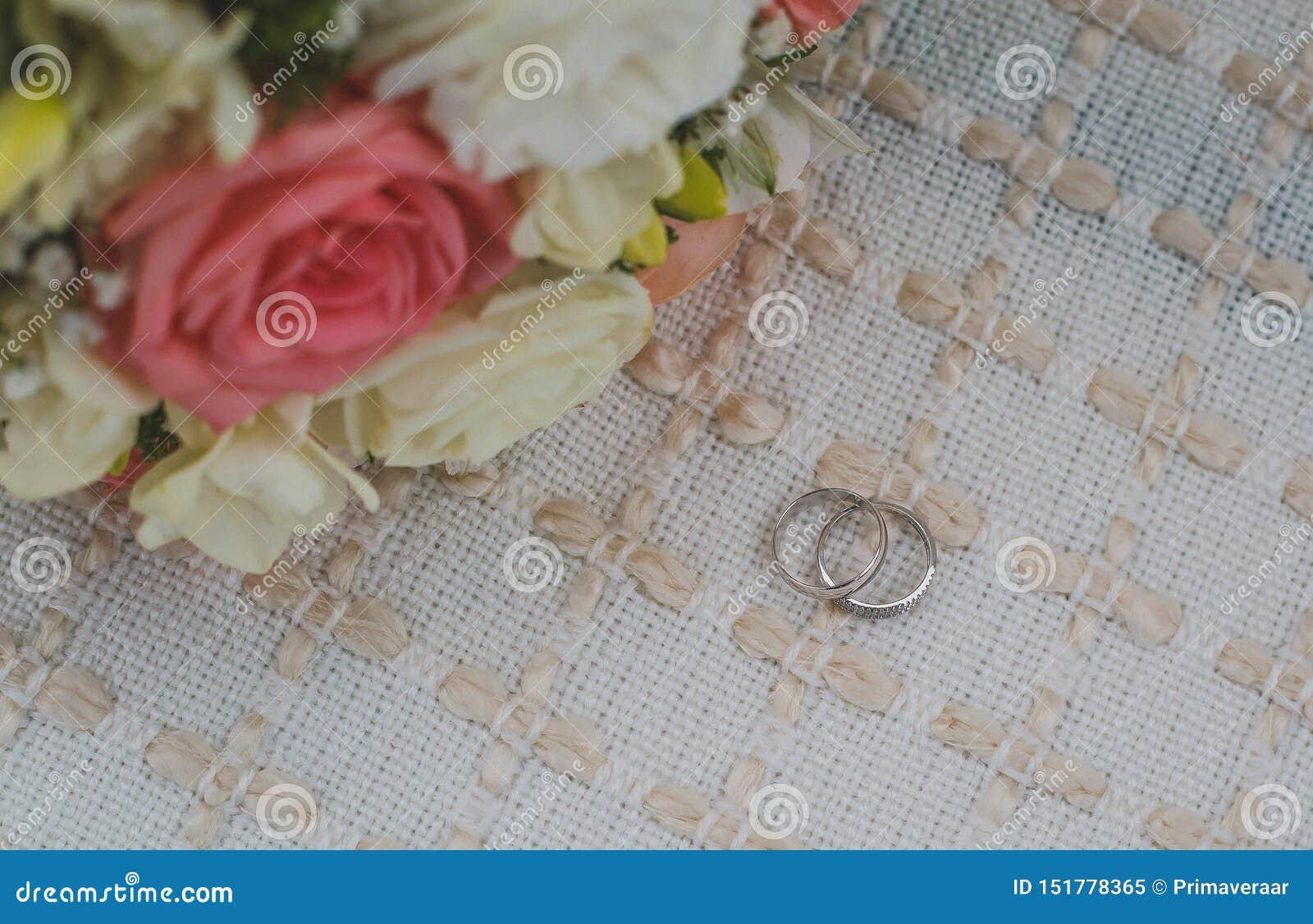Białego złota obrączki ślubne kłamają na beżowym dywaniku, bridal bukiet