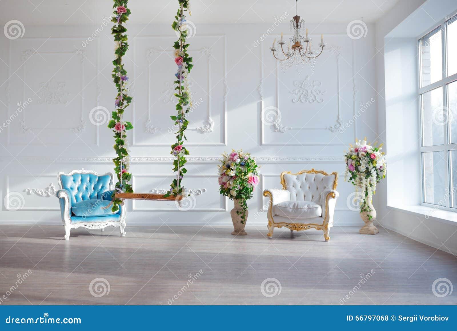 Białej skóry rocznika stylu krzesło w klasycznym wewnętrznym pokoju z dużą wiosną i okno kwitnie