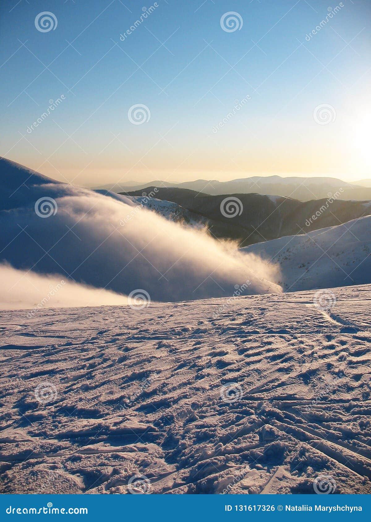 Biały śnieg zakrywający halni szczyty na wysokości Mgła płynie nad górą Opustoszały błękitny krańcowy zima krajobraz