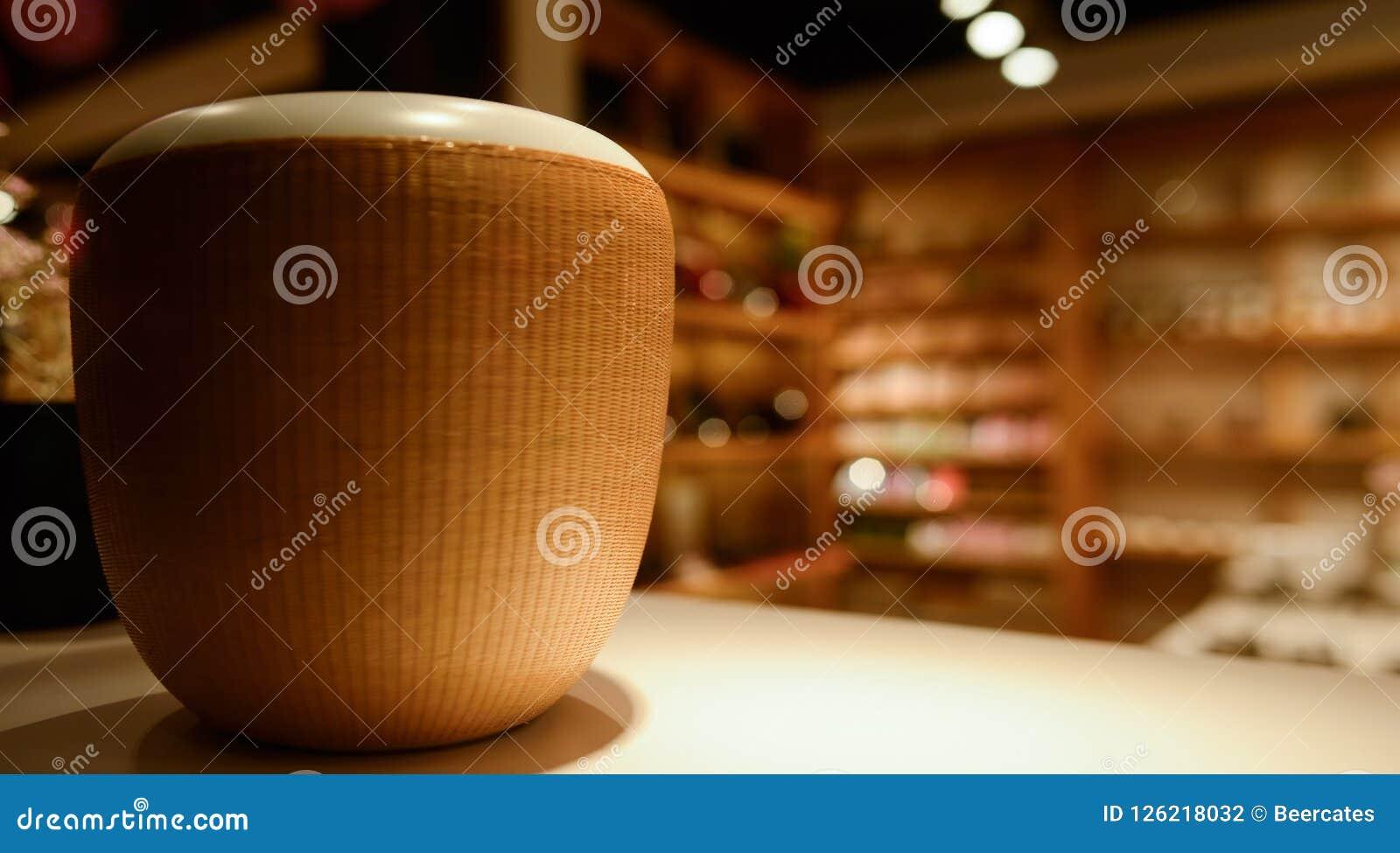 Biały ceramiczny łzawica z wyplatającą kurtką wewnątrz na stole