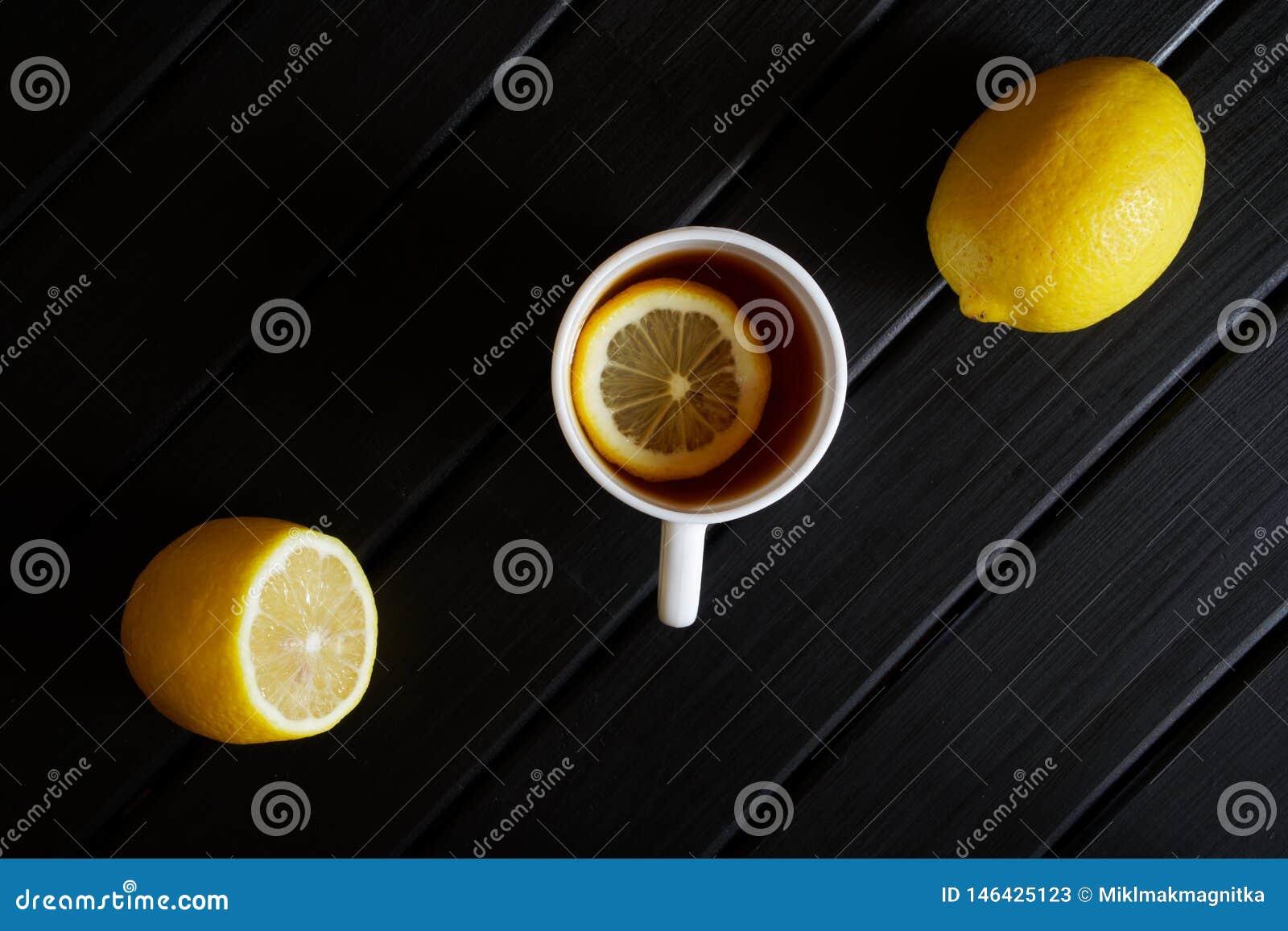 Biały kubek z czarną herbatą i cytryną na ciemnej drewnianej powierzchni na widok minimalista