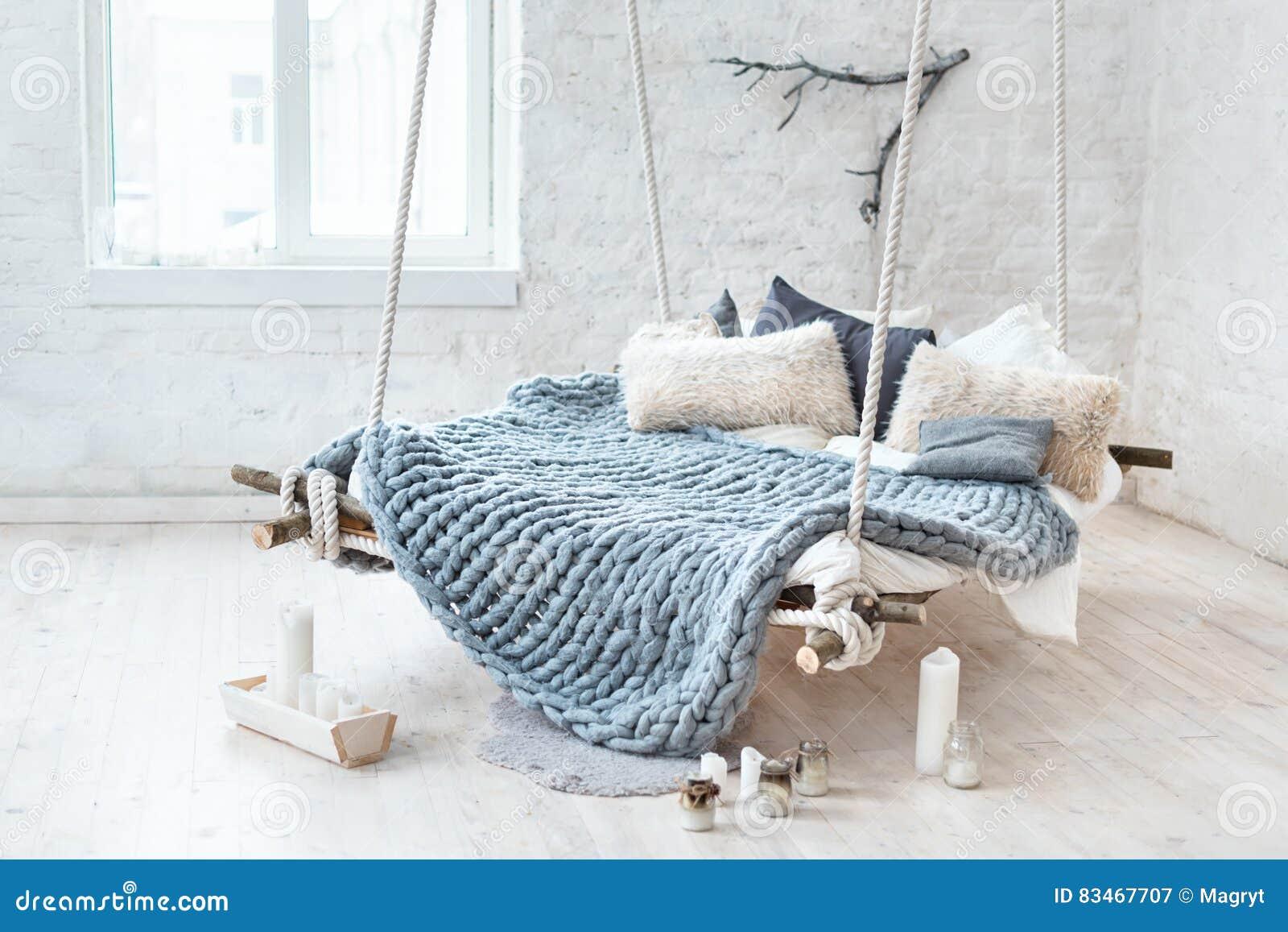 Biały loft wnętrze w klasycznym scandinavian stylu Wiszący łóżko zawieszający od sufitu Wygodnej ampuły fałdowa szara szkocka kra
