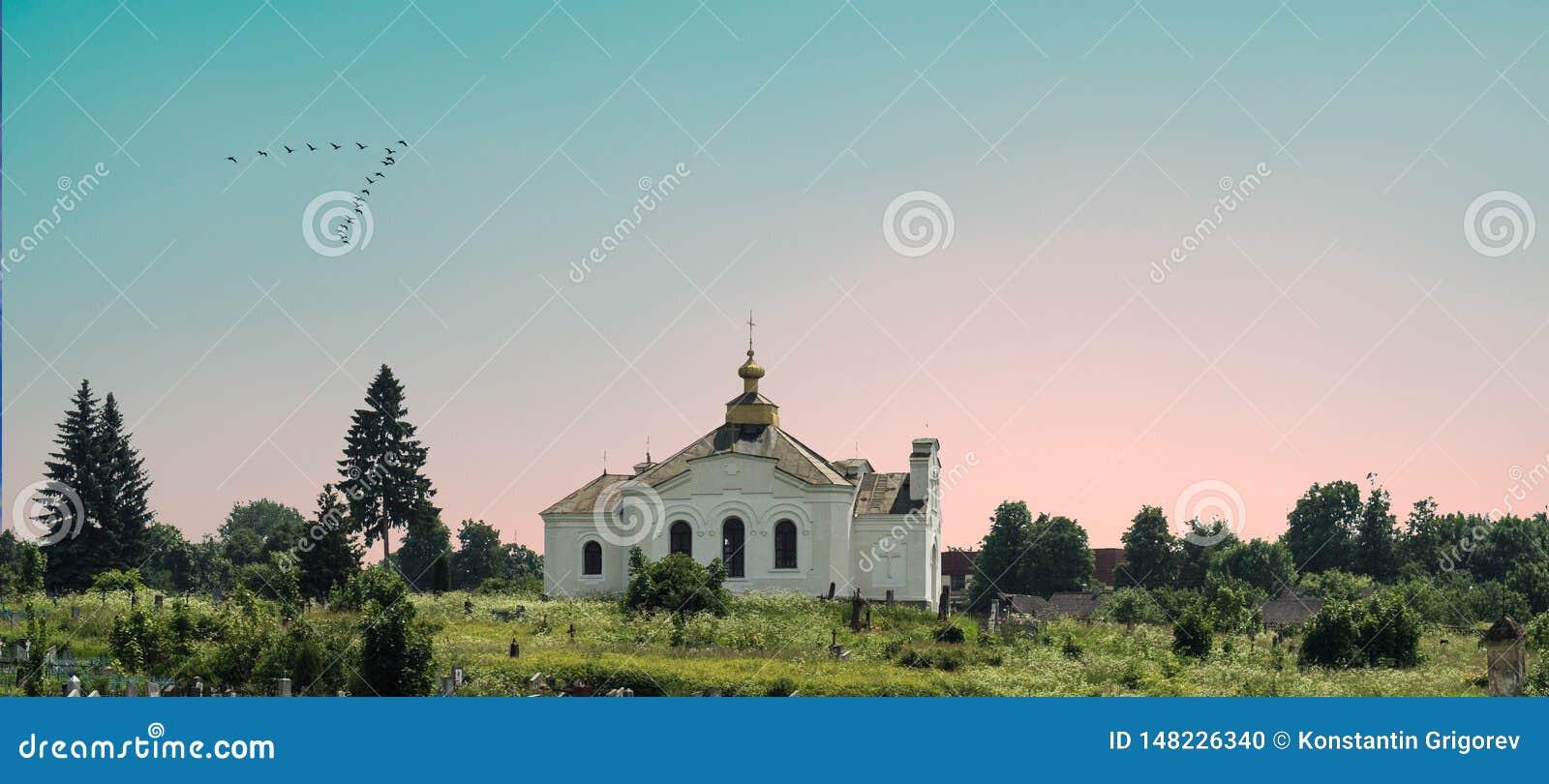 Biały ortodoksyjny kościół wśród drzew na tle piękne menchie i niebieskie niebo