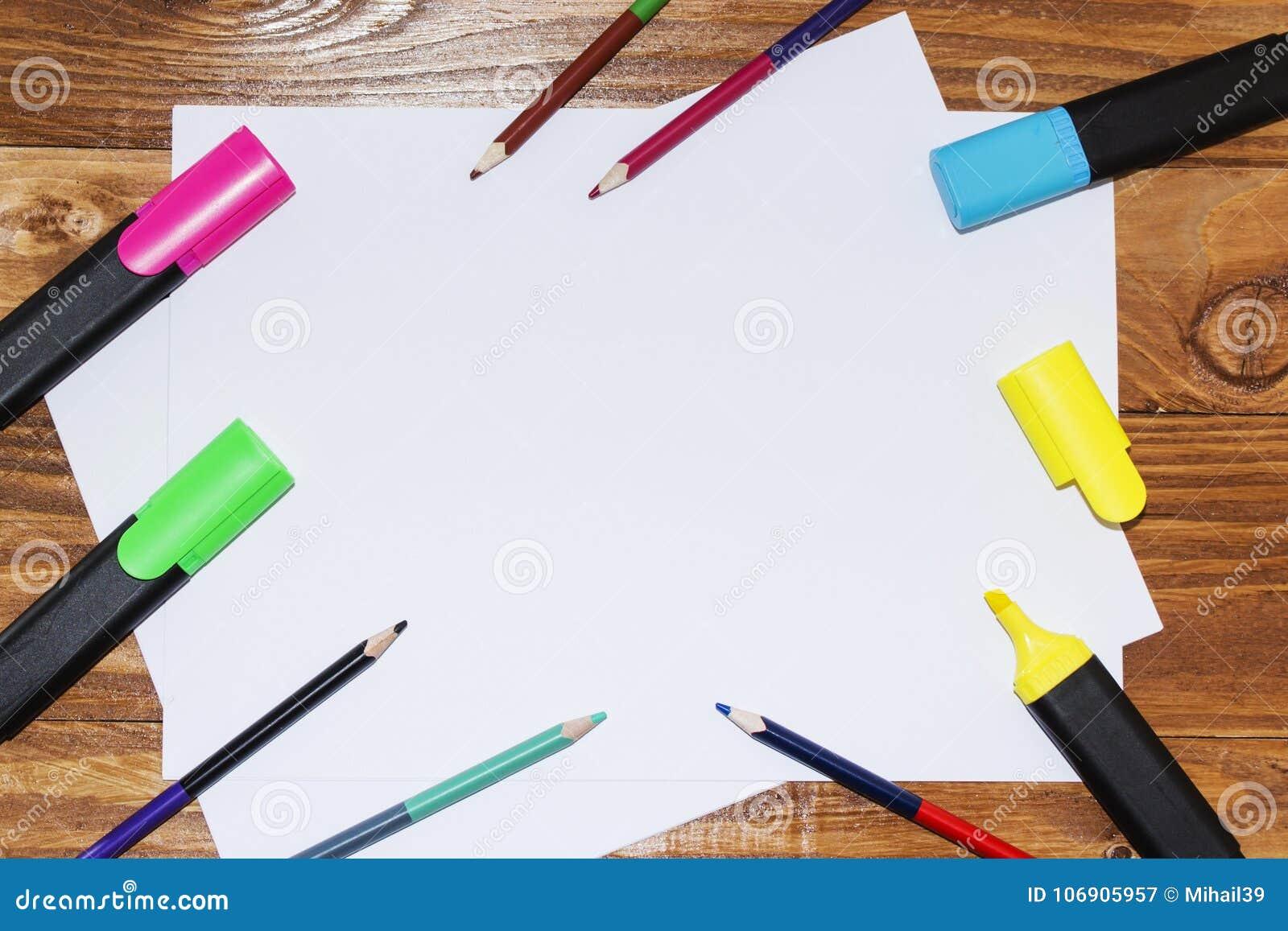 Biały prześcieradło papier kłaść na drewnianym stole, blisko, ołówki, markiery, pióra najlepszy widok