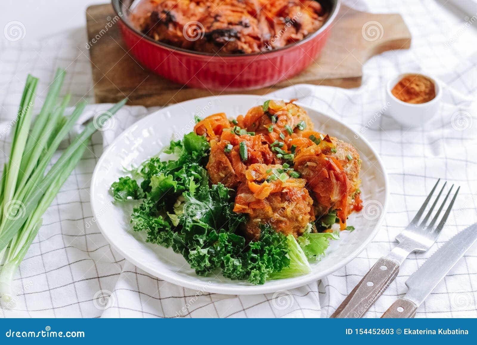Biały puchar domowi gotujący klopsiki z warzywami i sałatka liśćmi
