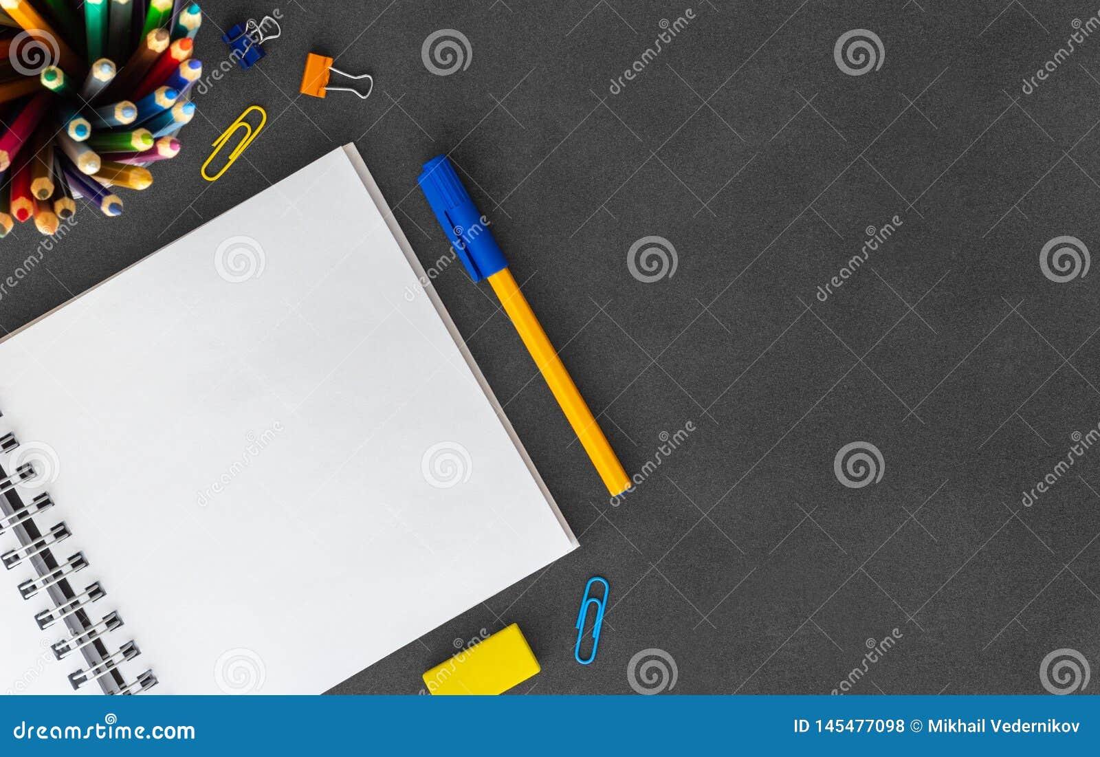 Biały puste miejsce spirali papieru notatnik z piórem, barwioni ołówki, gumka, papierowa kępa, papierowe klamerki na pustym