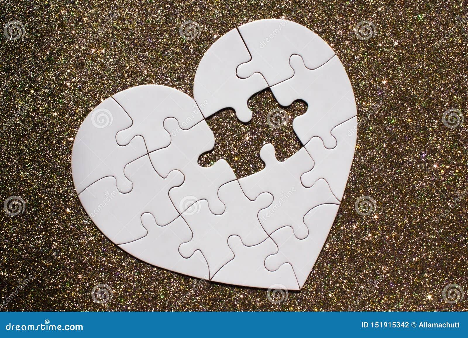 Biały serce kształtował łamigłówkę na złotym błyszczącym tle