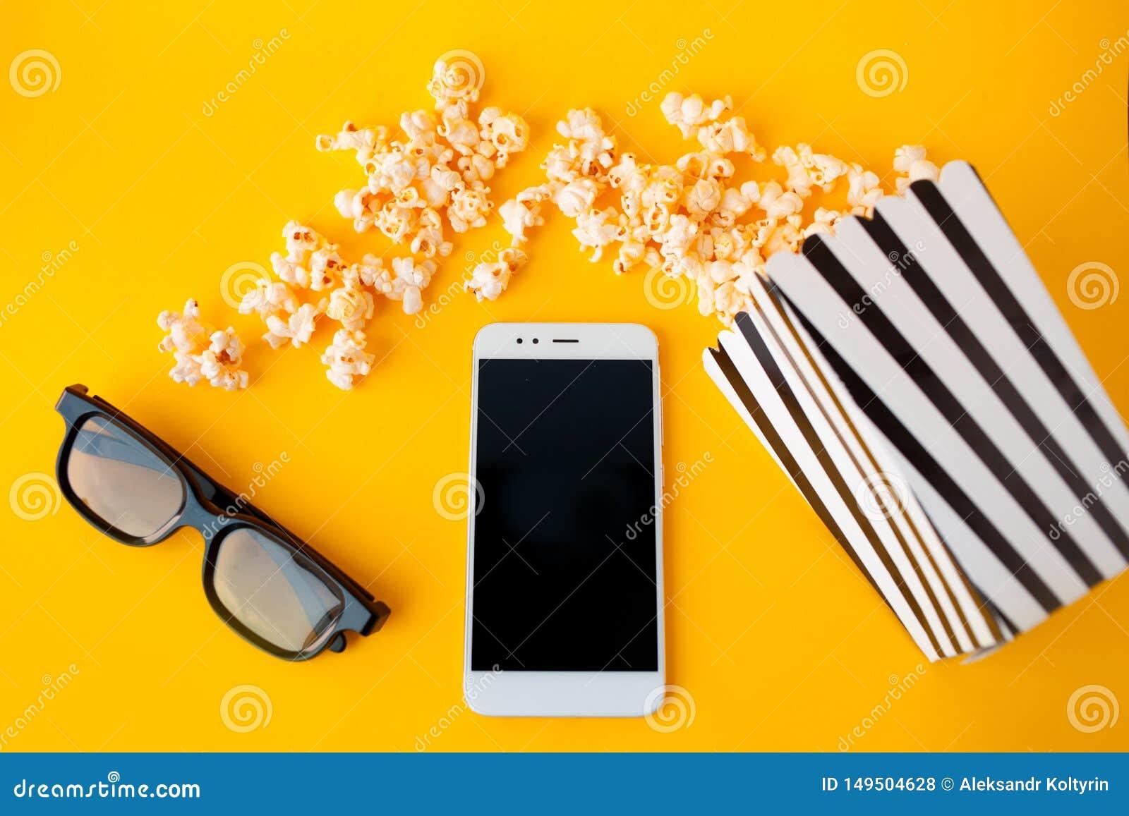 Biały smartphone, 3d szkła, czarny i biały pasiasty papierowy pudełko i rozrzucony popkorn, kłamamy na żółtym tle