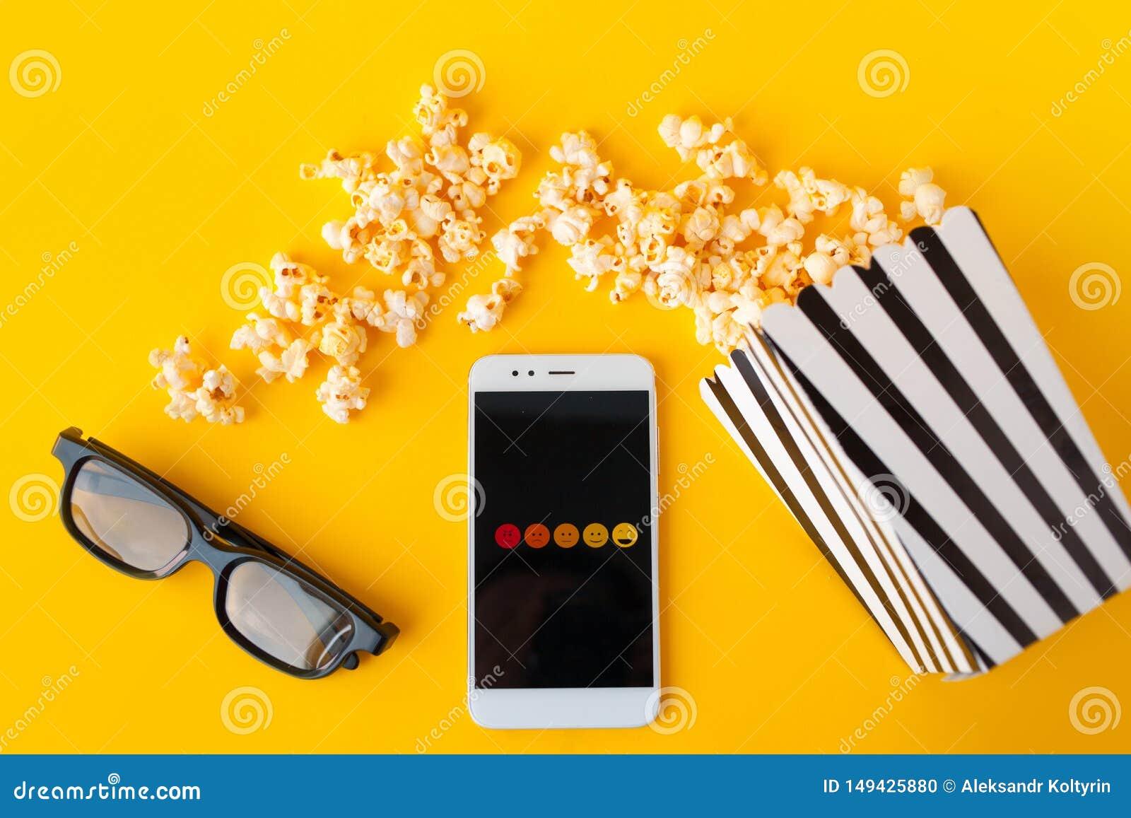 Biały smartphone z smilies na ekranie, 3d szkłach, czarny i biały pasiastym papierowym pudełku i rozrzuconym popkornie,