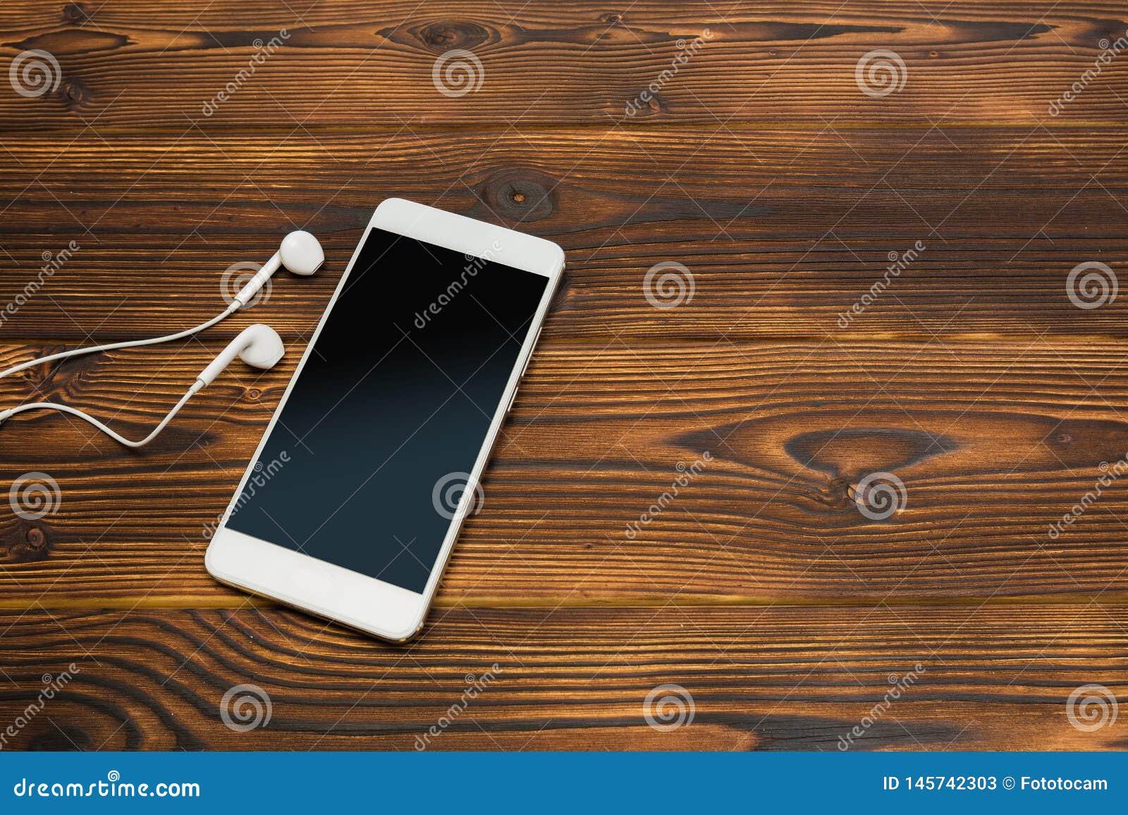 Bia?y smartphone z he?mofonami na drewnianym tle