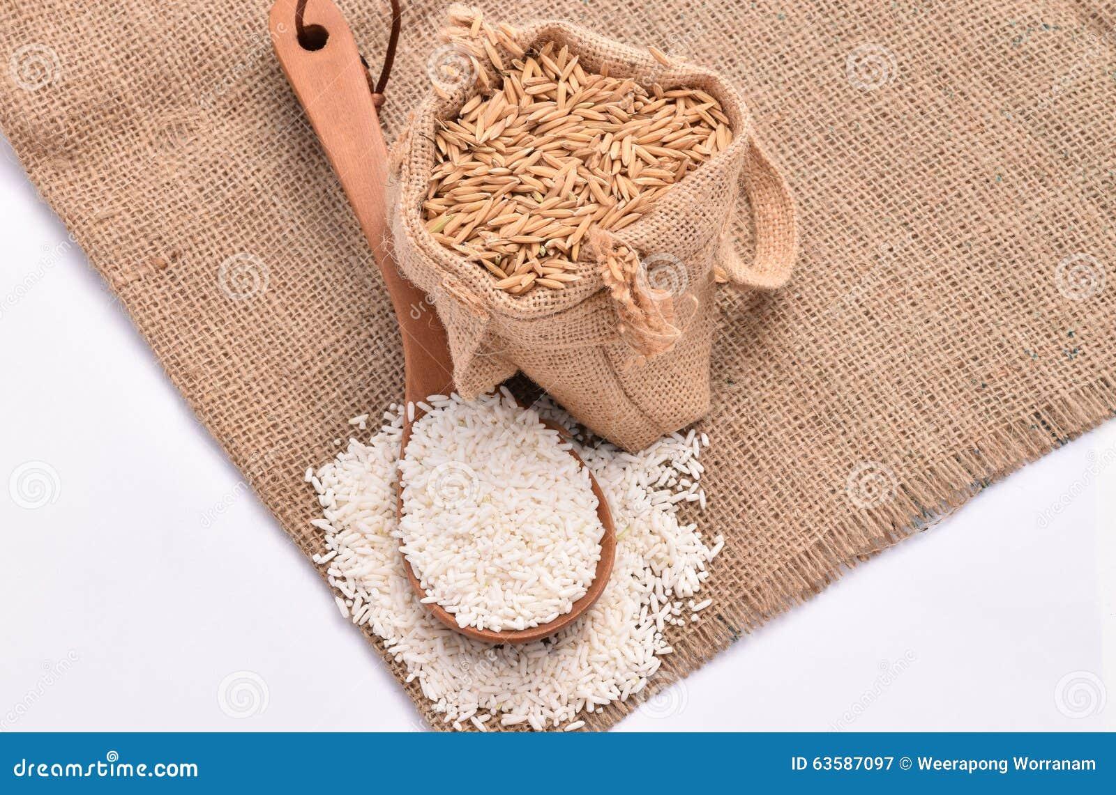 Biali irlandczyków ryż na drewnianej łyżce i konopie worku z brown irlandczyków ryż ziarnem na białym tle