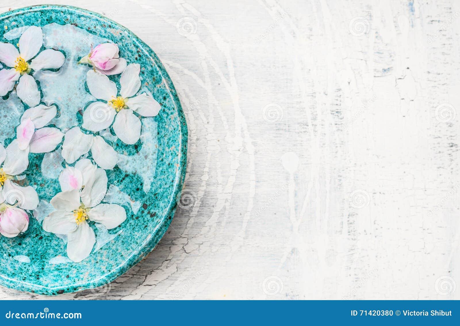 Biali kwiaty w turkusowej błękitne wody rzucają kulą na lekkim podławym modnym drewnianym tle, odgórny widok, miejsce dla teksta
