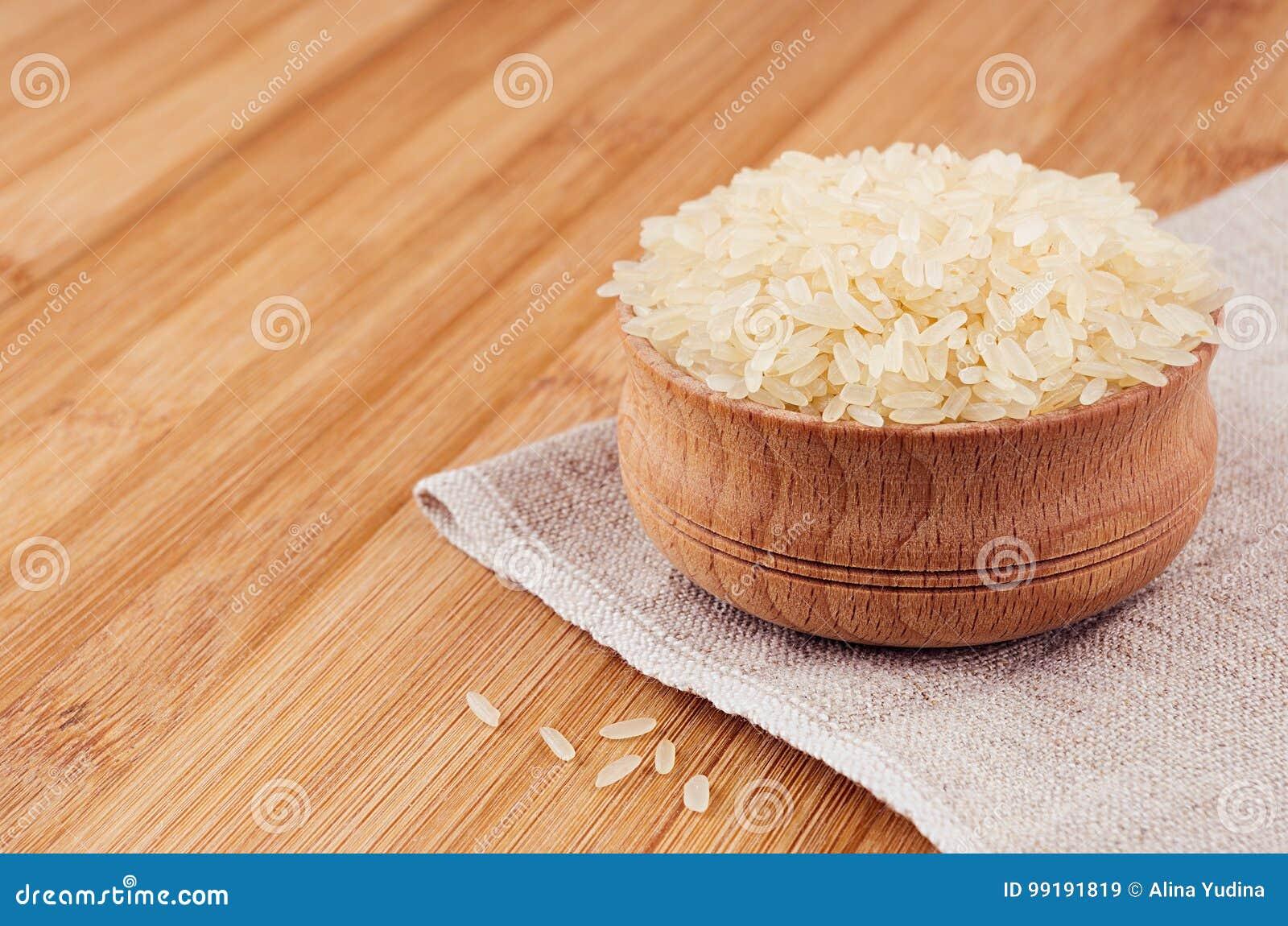 Biali ryż basmati w drewnianym pucharze na brown bambus desce, zbliżenie Wieśniaka styl, zdrowy żywienioniowy zboża tło