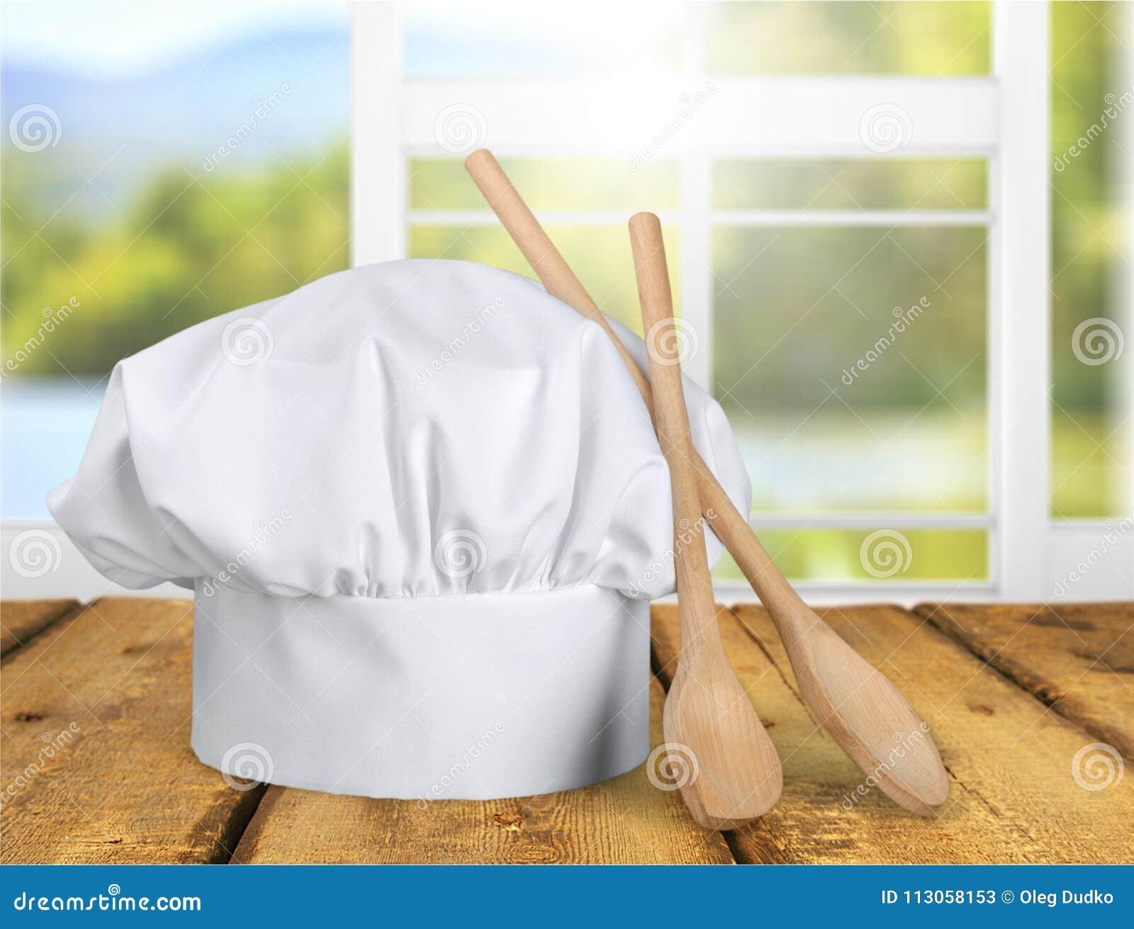 Biali szefów kuchni naczynia na stole i kapelusz