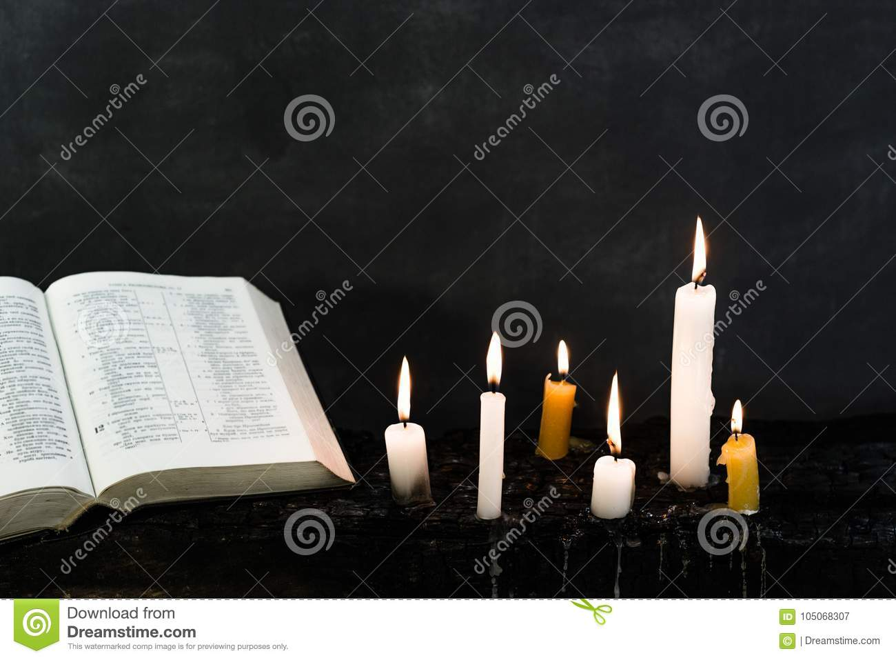 Candles on an old wooden burnt table. Beautiful dark background. Religious concept.
