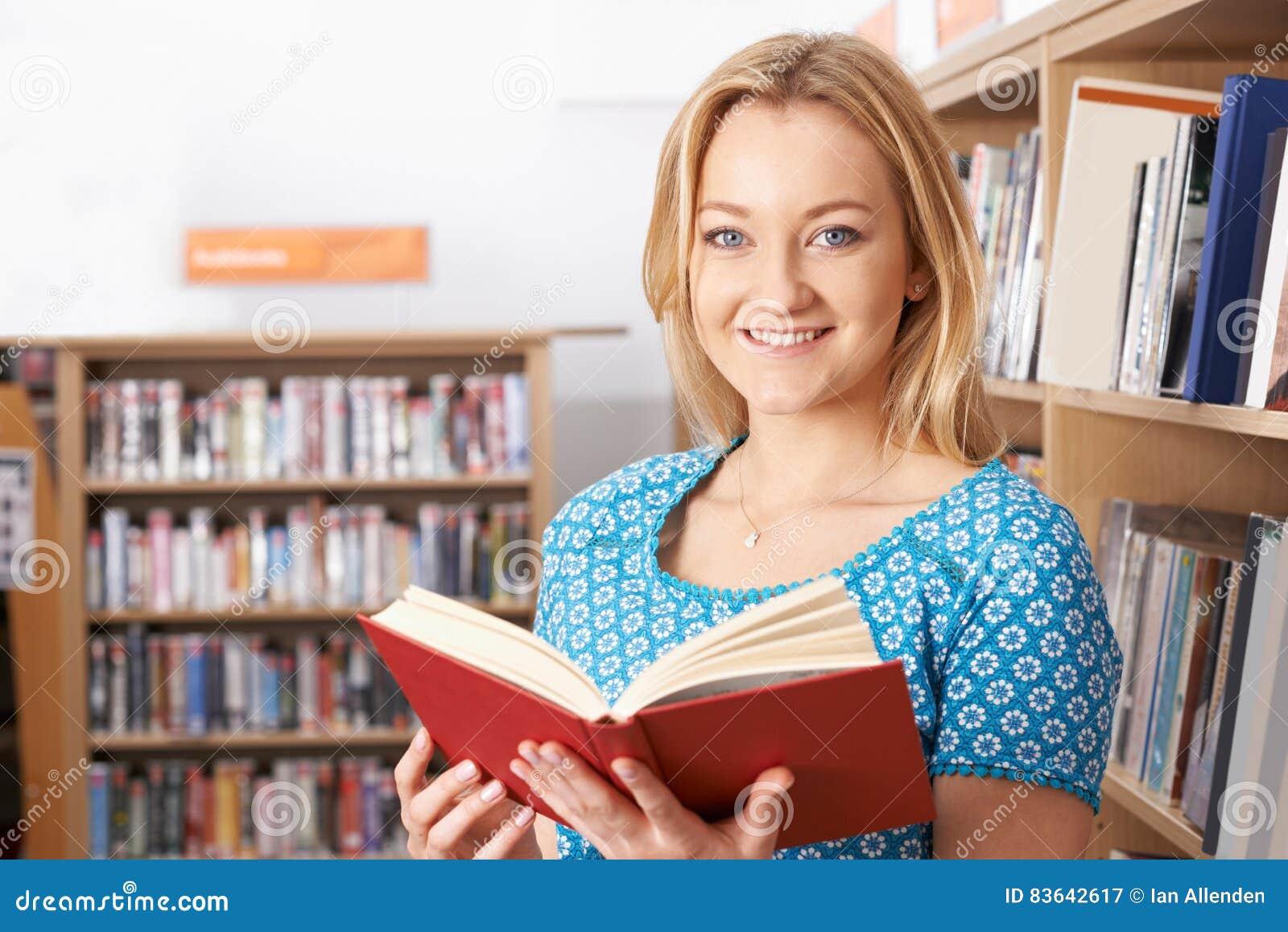 Biblioteca de Reading Book In do estudante fêmea