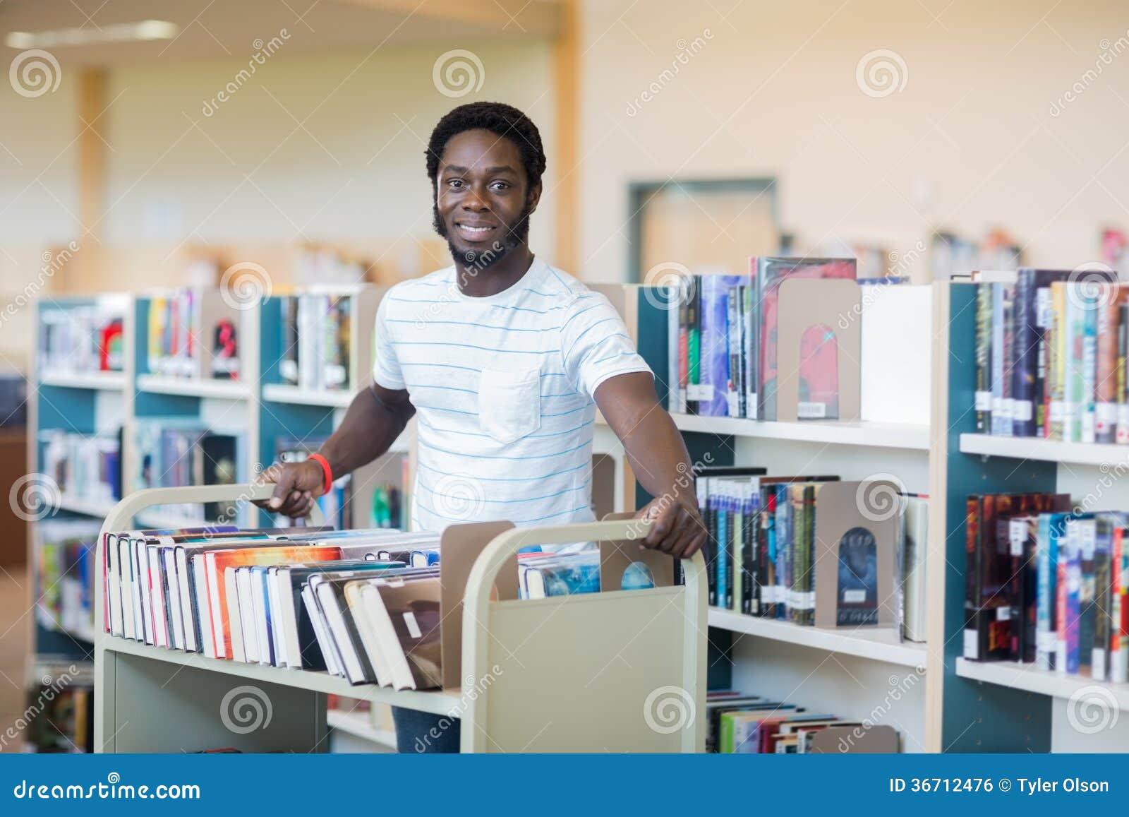 BibliotekarieWith Trolley Of böcker i arkiv