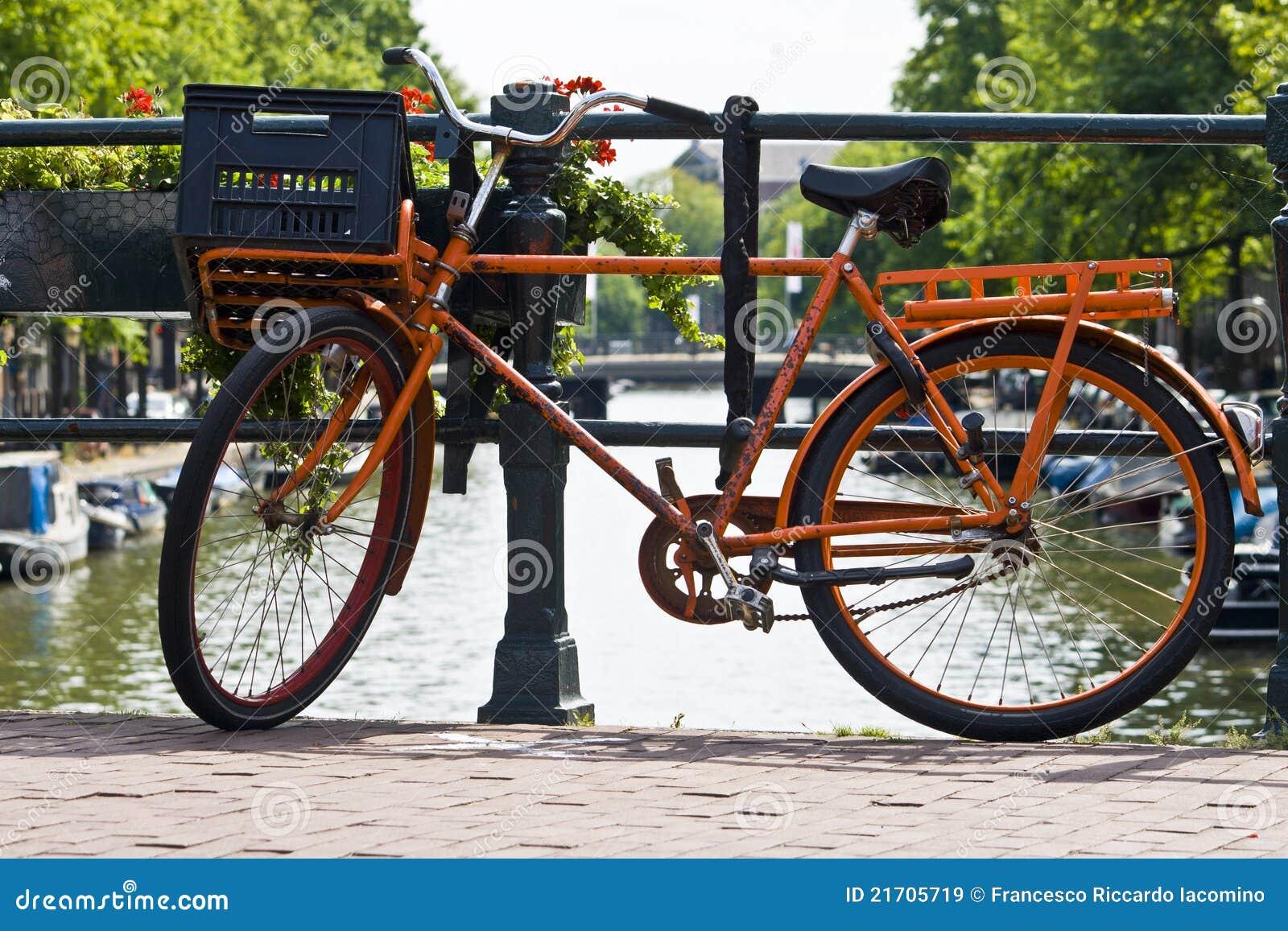 Bici arancione su un canale di amsterdam immagini stock for Affitto bici amsterdam