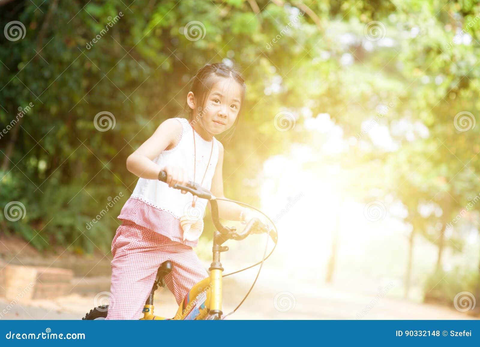 Bicicleta asiática del montar a caballo del niño al aire libre