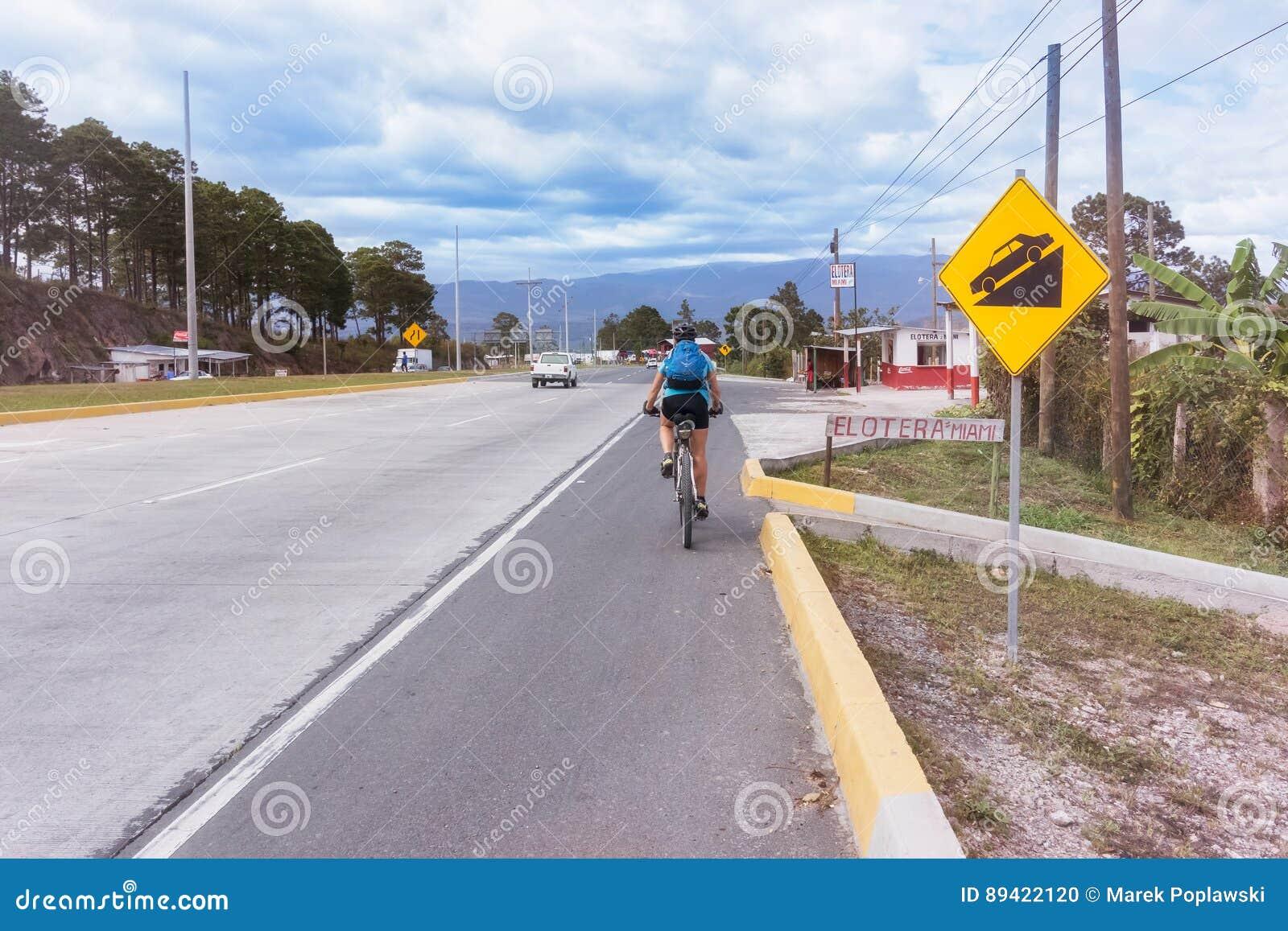 Bicicleta da equitação em uma estrada em Honduras centrais