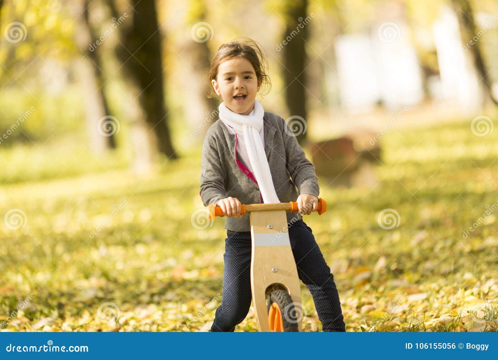 Bicicleta da equitação da menina no parque do outono