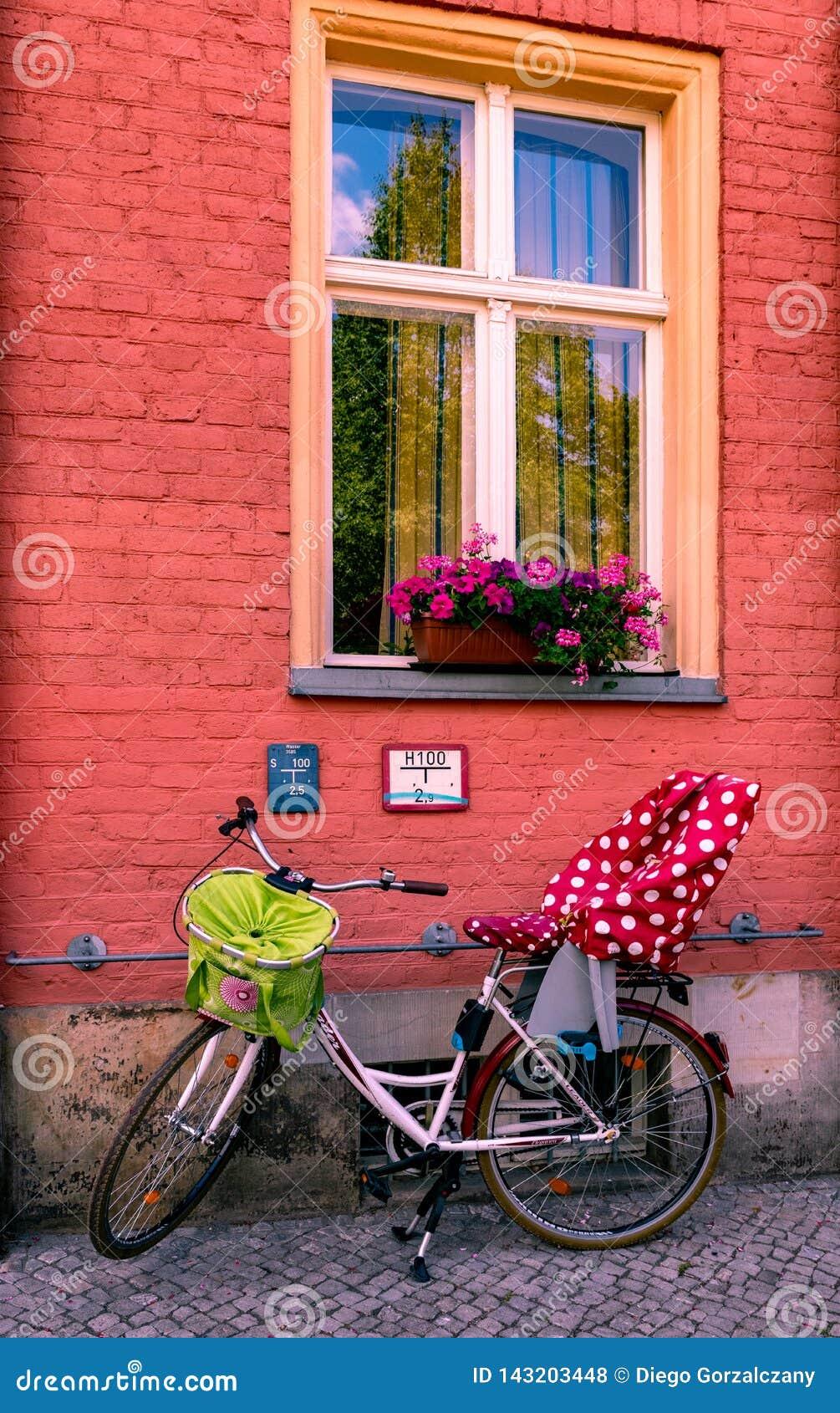 Bicicleta da família que descansa na parte dianteira de uma casa de potsdam
