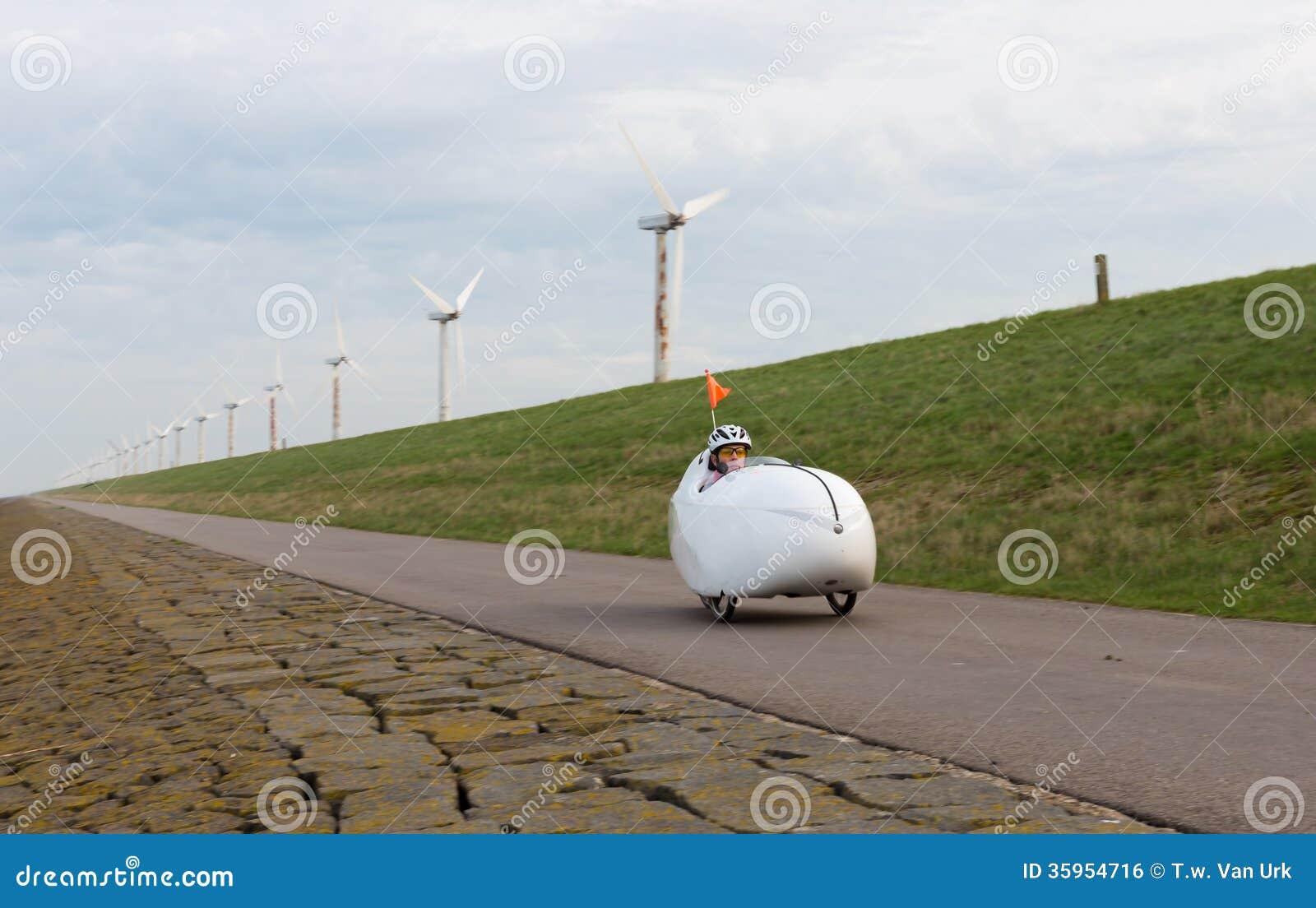 Bicicleta de Velomobile a lo largo de la costa holandesa