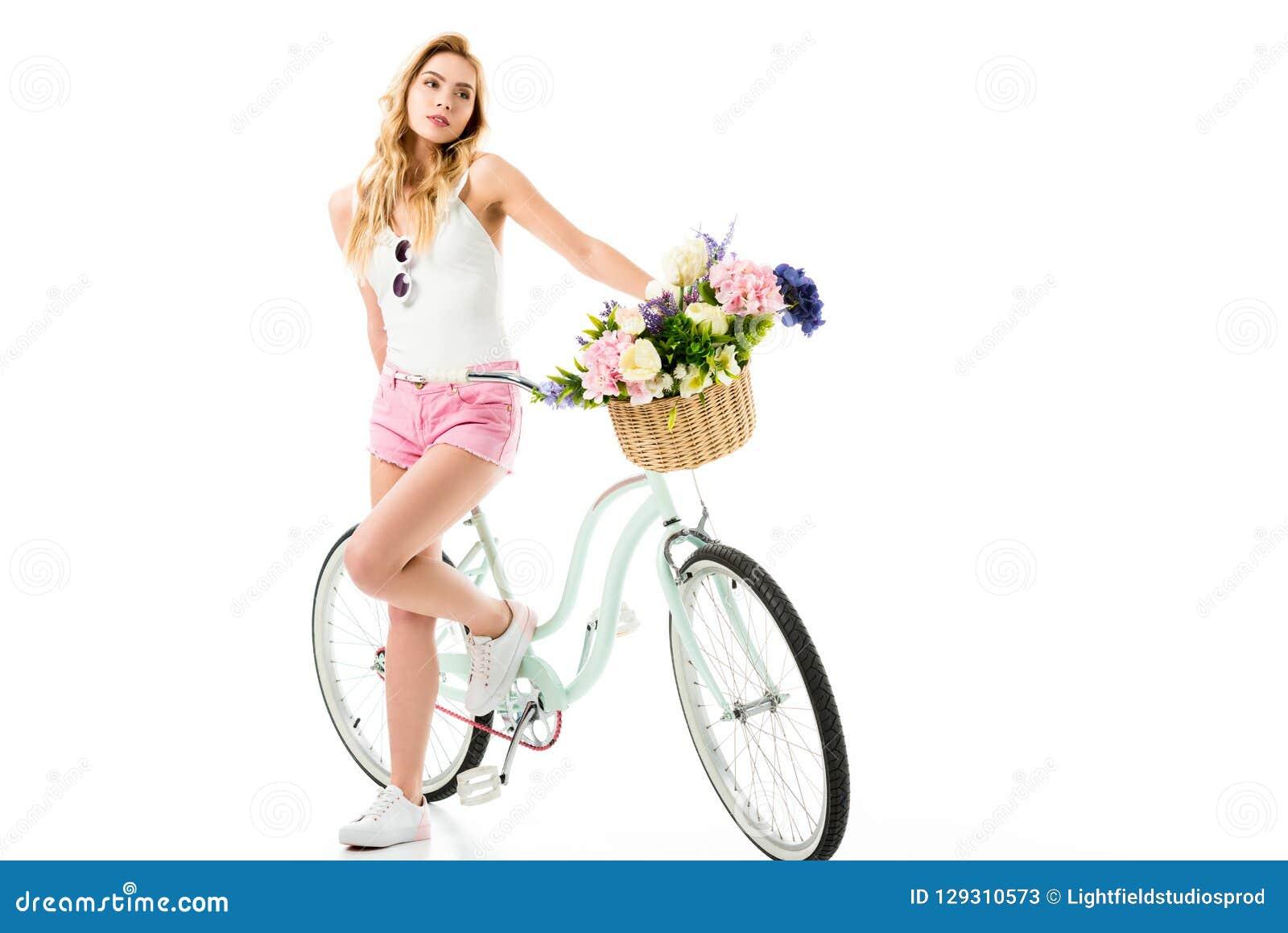 Bicicleta del crucero de la chica joven que hace una pausa con las flores en cesta